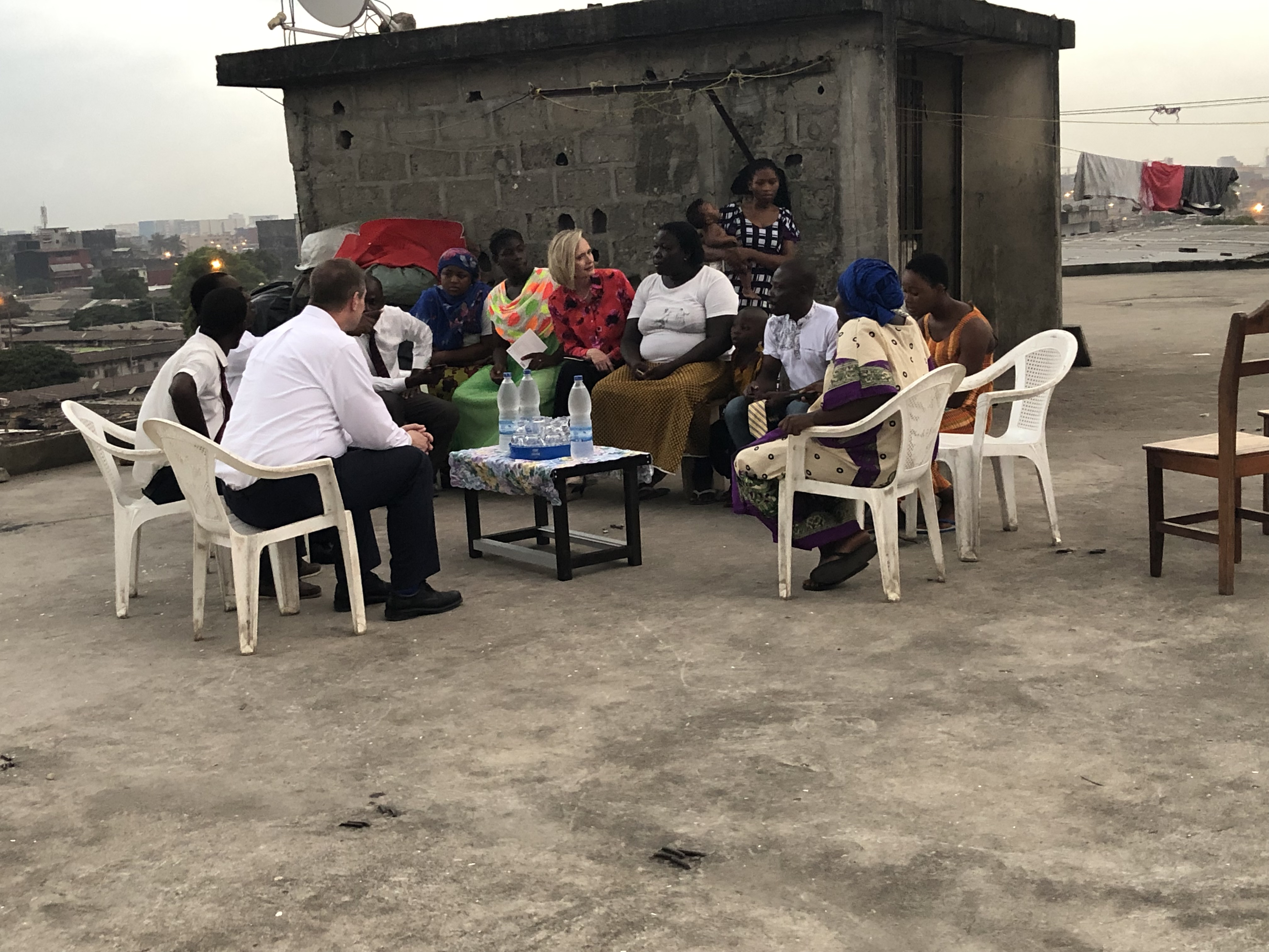 As the sun goes down, Sister Bonnie H. Cordon, Young Women general president, meets with a family on the roof of a building in Abidjan, Côte d'Ivoire, Friday, March 8, 2019.
