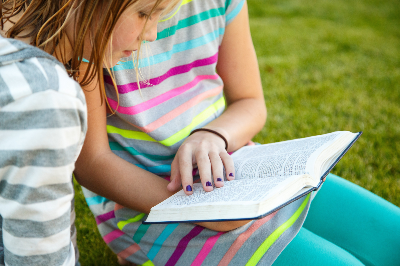 Two young girls read from the Book of Mormon.