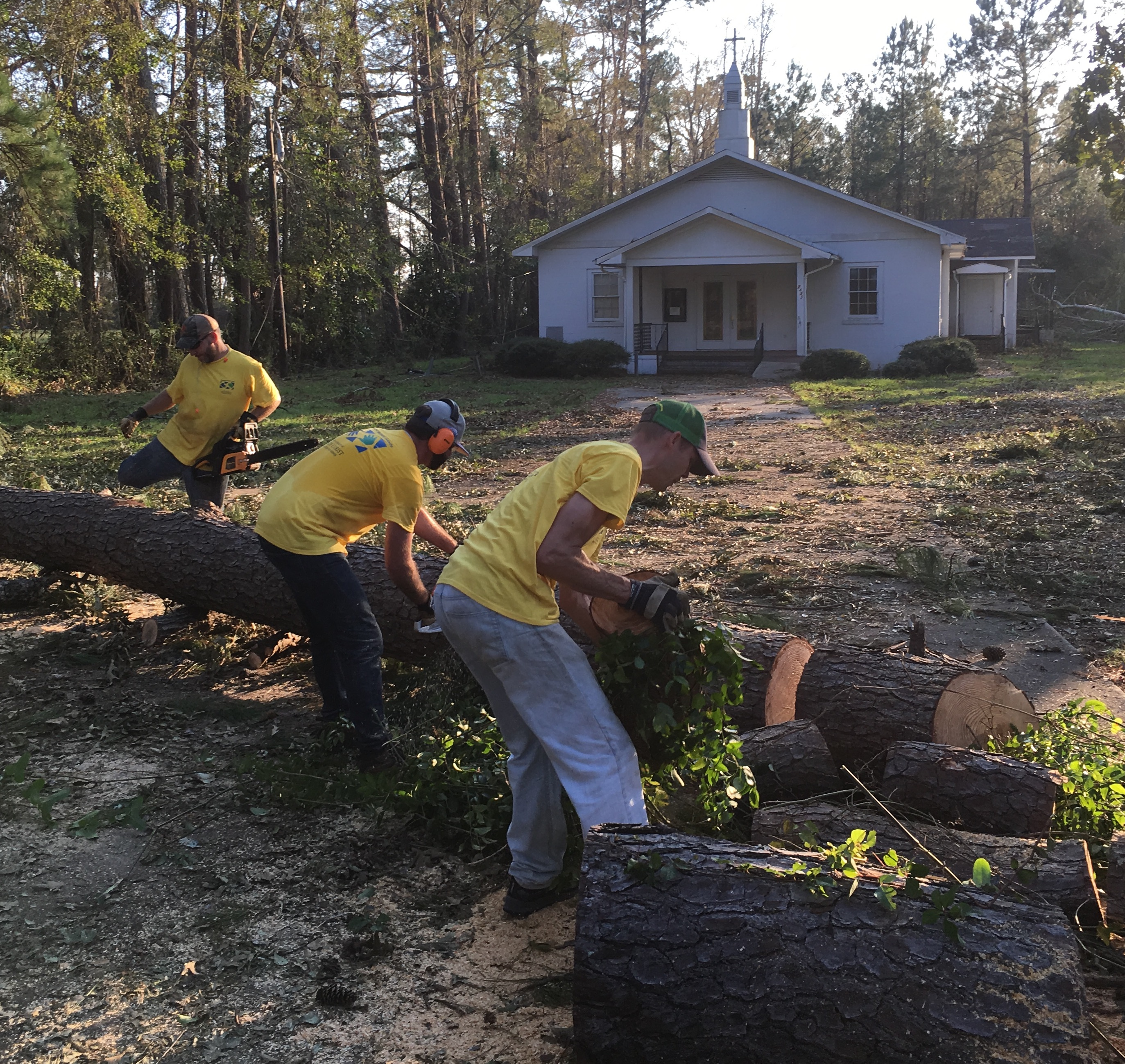 A Latter-day Saint Helping Hands work crew chops up a fallen tree outside a local church in Wilmington, North Carolina.
