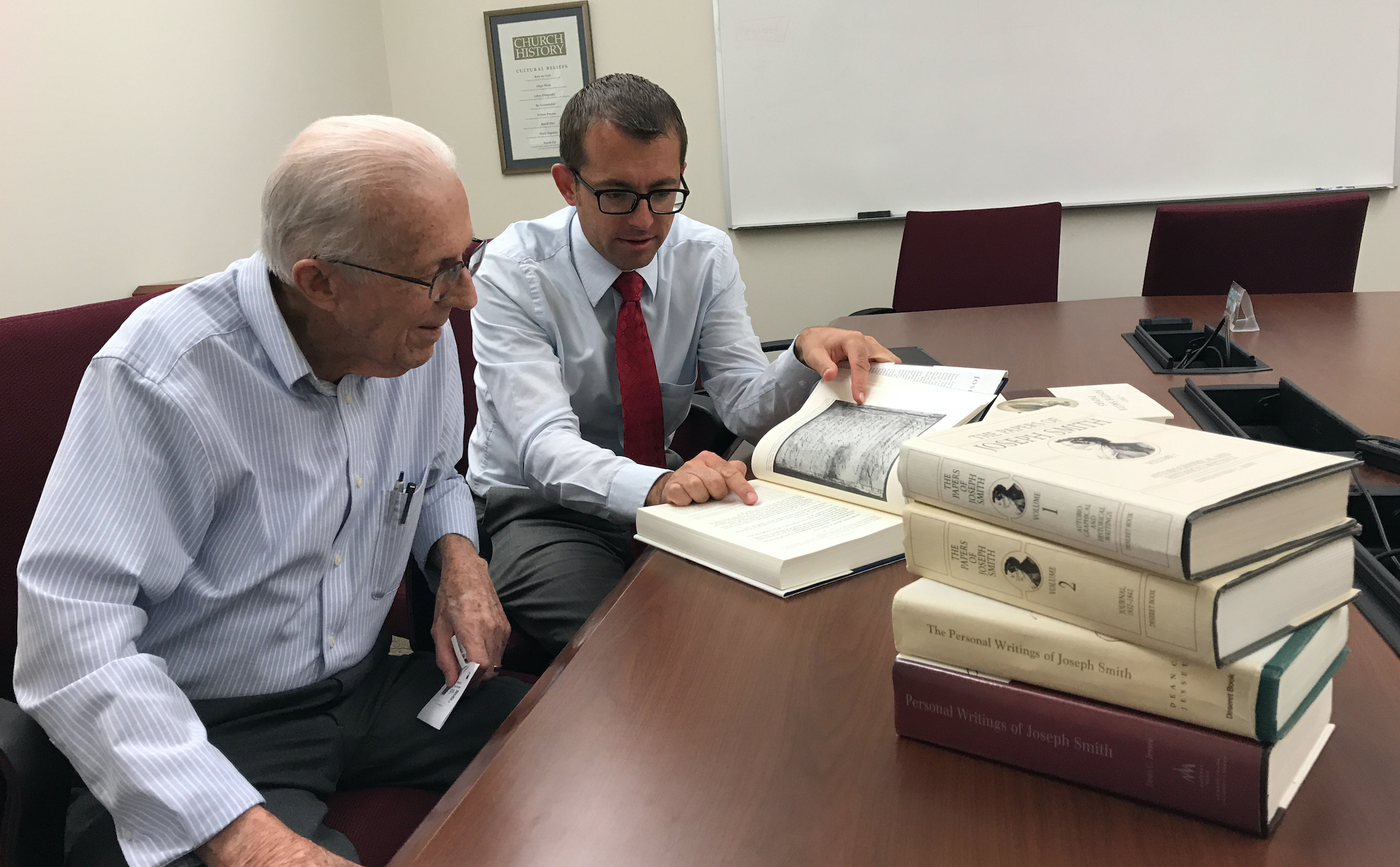 Dean C. Jessee, left, is one of the founders of the Joseph Smith Papers project. He and Nathan Waite, an associate editorial manager, look through some of the recent volumes of the Joseph Smith Papers.