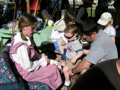 Young women in the El Cajon Stake booth make pioneer dolls in a demonstration for visitors to the Mormon Battalion commemoration in San Diego.