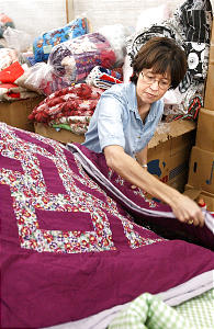 Penny Brown folds quilts in the Quilt Room at the Humanitarian Service Room at Deseret Industries in Murray on December 4, 2001.