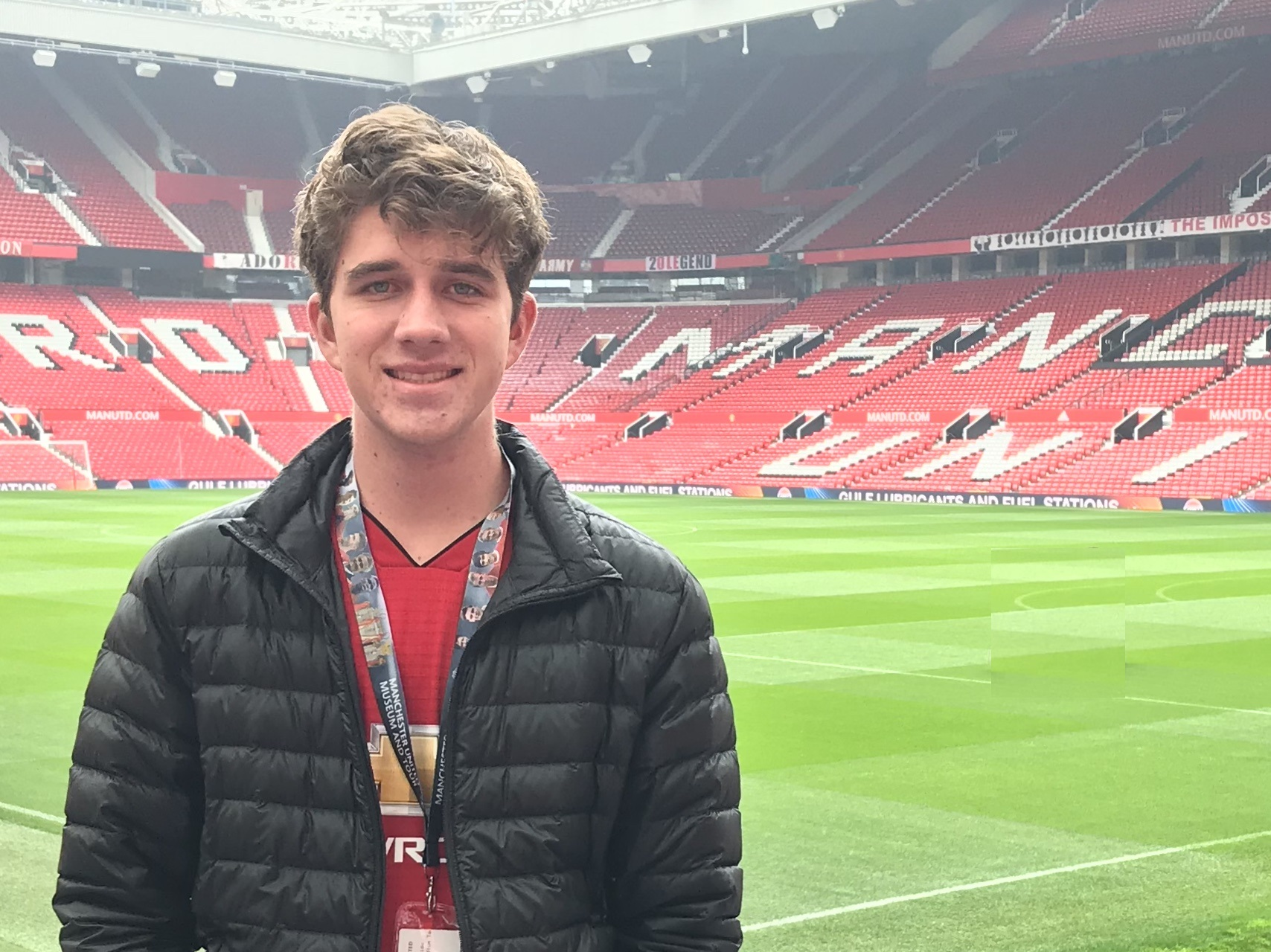 Sam Williams stands on the field at Old Trafford Stadium, the world-famous home of Manchester United.