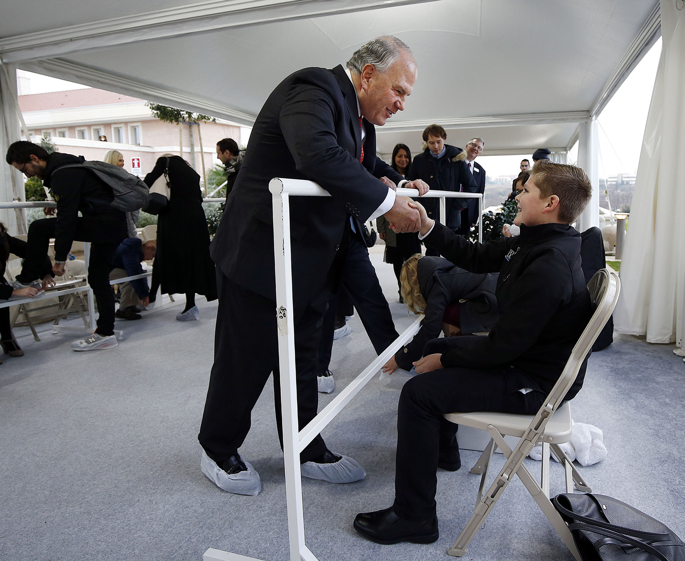 Elder Ronald A. Rasband of the Quorum of the Twelve Apostles of The Church of Jesus Christ of Latter-day Saints talks with Bryant Van Tassell after receiving shoe covers from him during the open house for the Rome Italy Temple on Monday, Jan. 14, 2019.