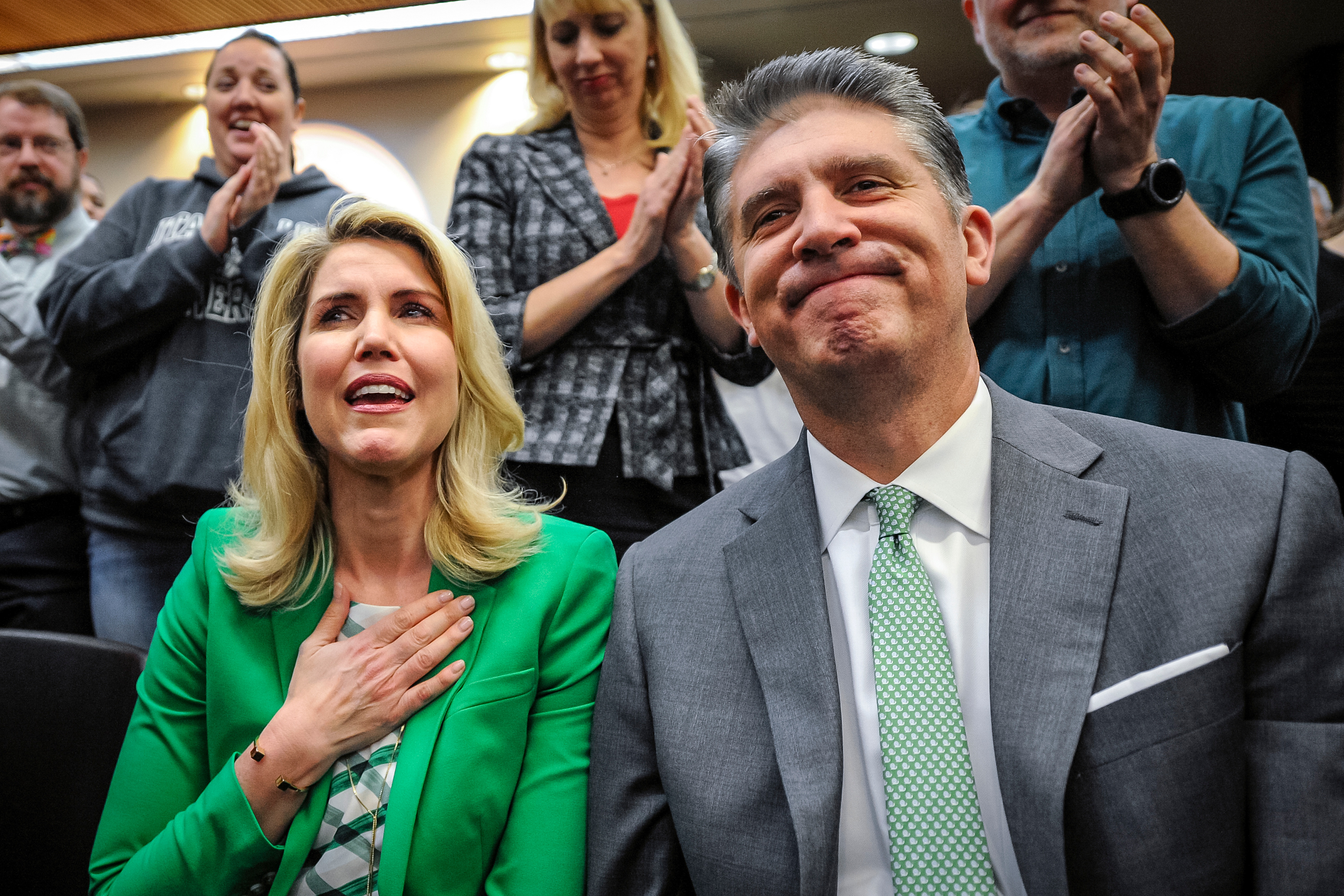 Paige Holland, left, and outgoing President Matthew S. Holland react when thanked for their service towards the university at the public meeting of the Board of Trustees where Astrid S. Tuminez is introduced as the seventh President of Utah Valley University in Orem on Friday, April 20, 2018.