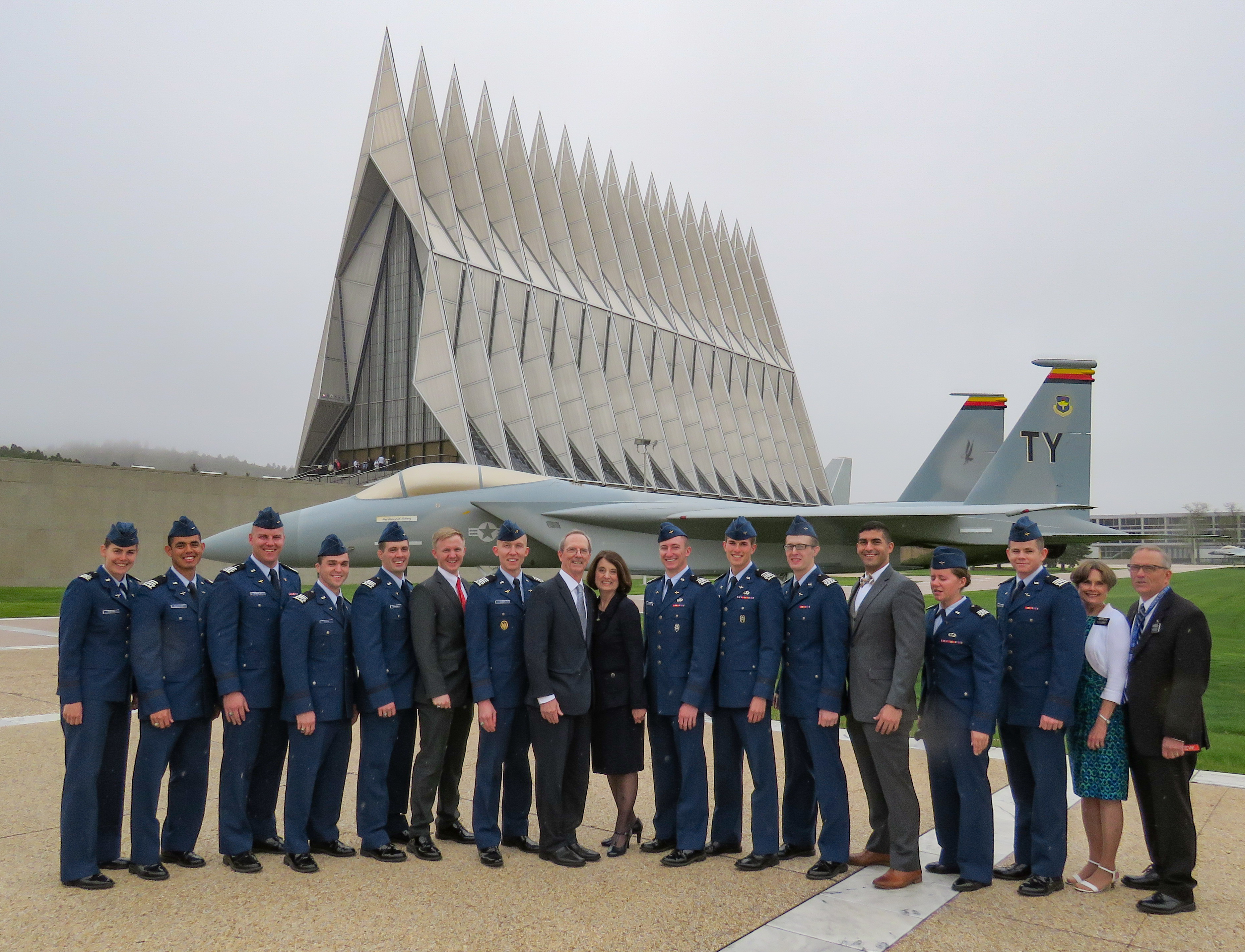 The drizzle doesn't dampen the spirits of seniors from the graduating class of 2018 who stand with Brother Tad R. Callister and Sister Kathryn S. Callister and Brother and Sister Lee, LDS Distinctive Religious Group Leaders at USAFA, in front of the historic chapel.