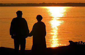 City Desk and/or Church News--Elder Chad and Sister Marilyn Price watch the sunset on the Mississippi River prior to Sunset on the Mississippi River program June 24nd, 2002. Allred/photo (Submission date: 06/24/2002)