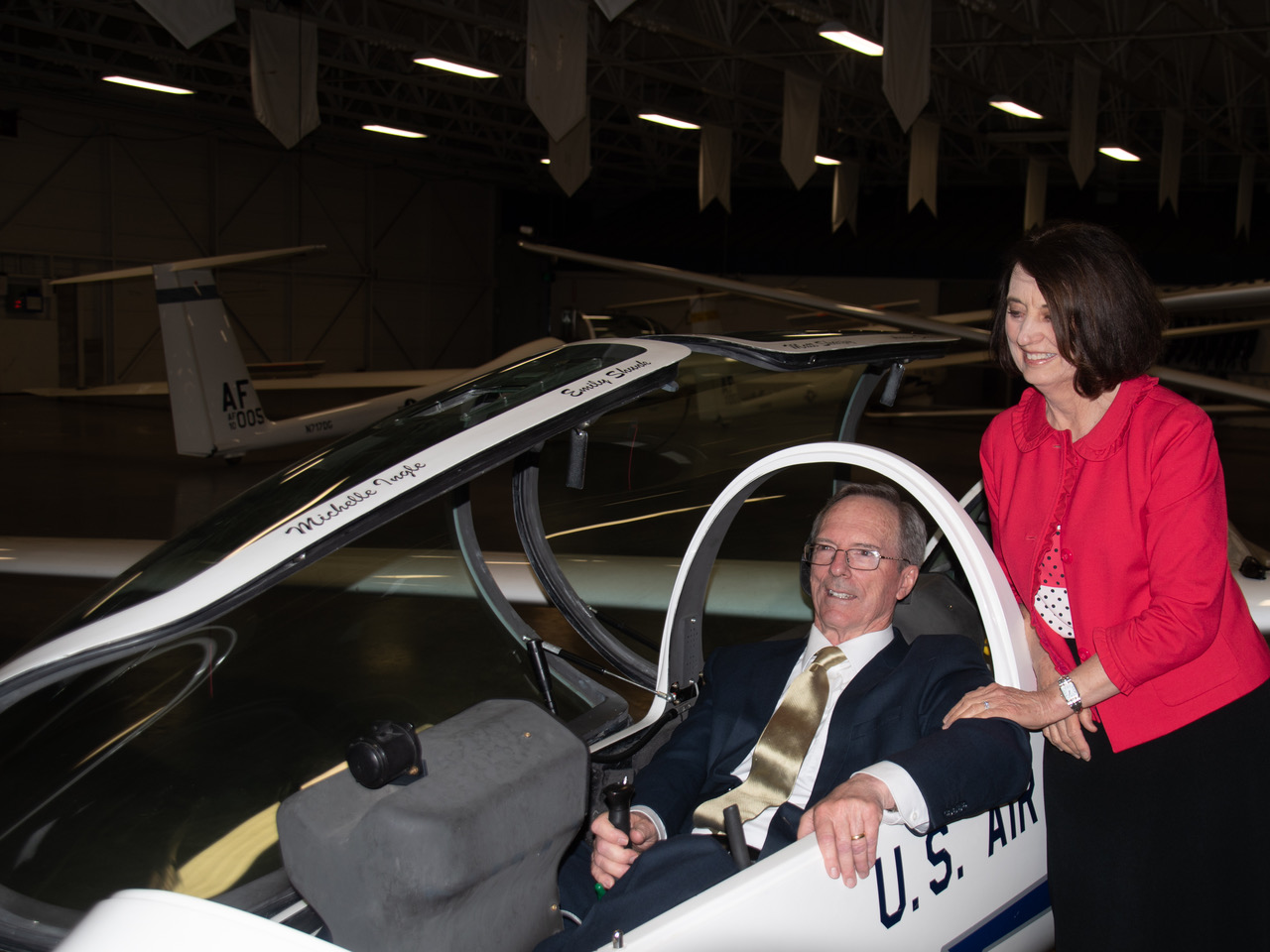 Sister Kathryn S. Callister watches in anticipation as Brother Callister takes the controls of a practice glider used to train future pilots at USAFA.