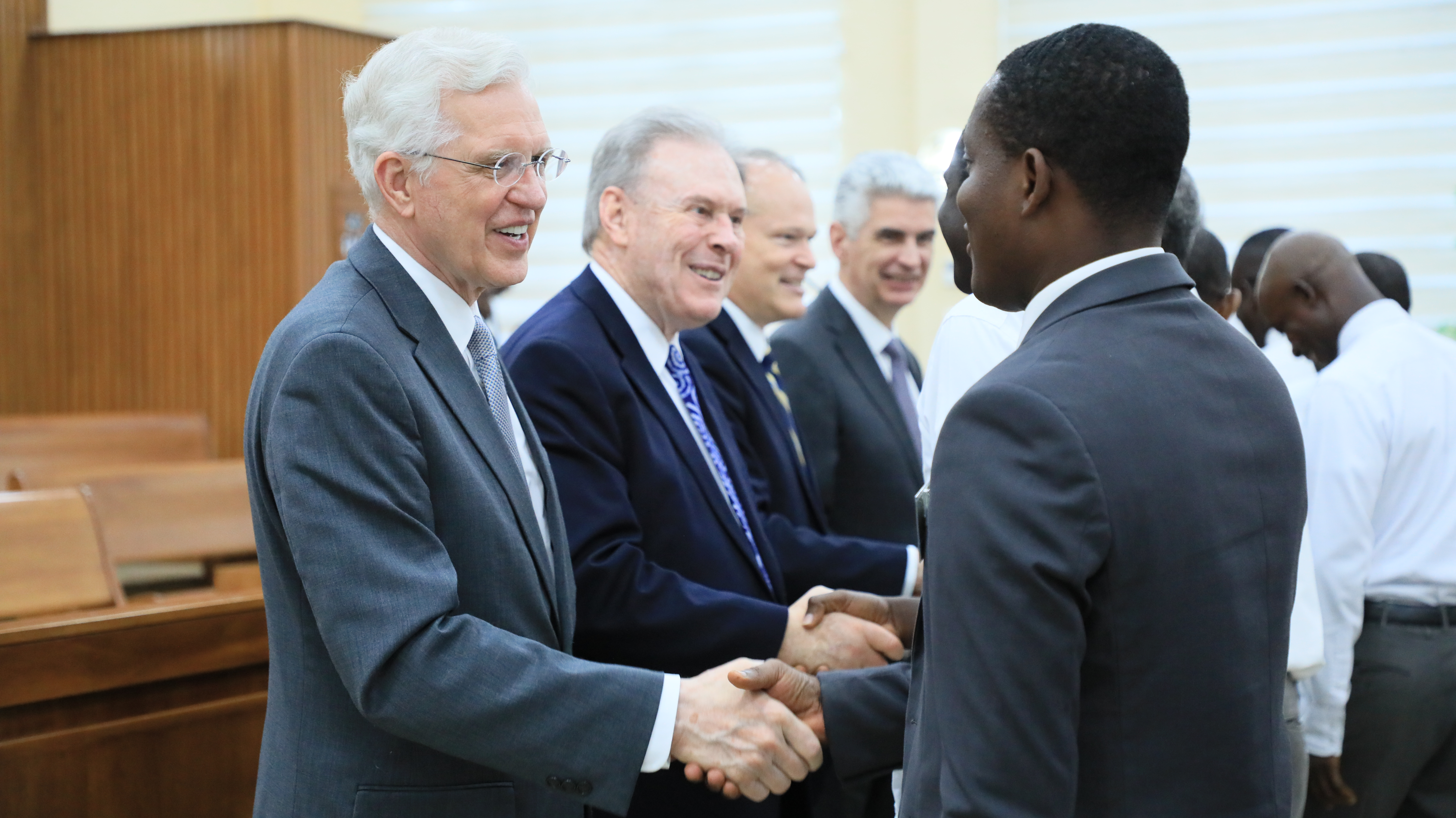 From left, Elder D. Todd Christofferson, Elder Terrence M. Vinson, Elder Marcus B. Nash and Bishop Gérald Caussé shake hands with members following a May 26, 2019, leadership conference in Accra, Ghana.