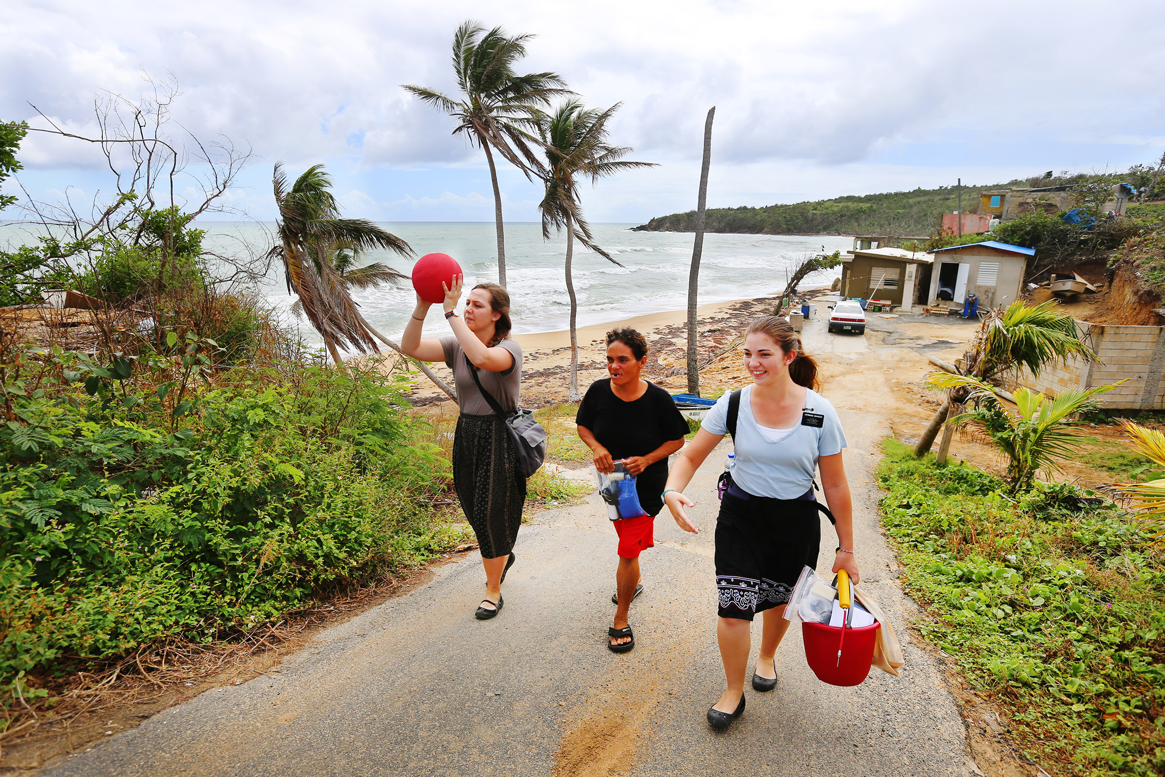 Sister's Mary Ruff from Midvale Utah, and Erin Bianucci from Layton Utah, talk with Miraida Ortiz as they walk up a small ocean side road in Puerto Rico on Saturday, Feb. 17, 2018.