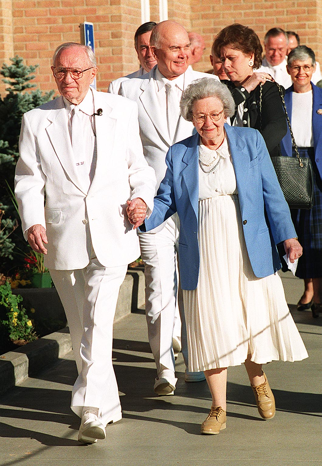 President and Sister Hinckley hold hands as they walk out of the Vernal Utah Temple on Nov. 2, 1997.