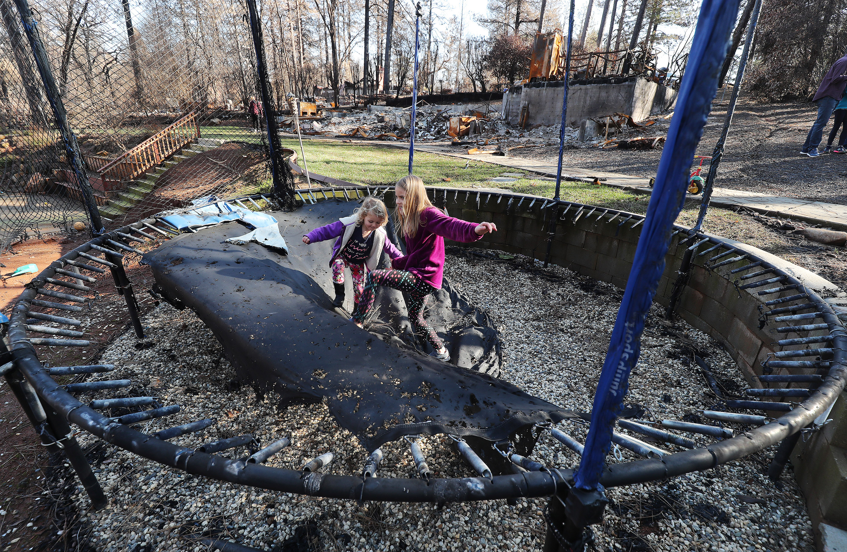 Aylee and DeLynn Chatfield play in their burned trampoline in Paradise, California, on Saturday, Jan. 12, 2019, two months after the Camp Fire destroyed more than 18,000 homes and businesses.