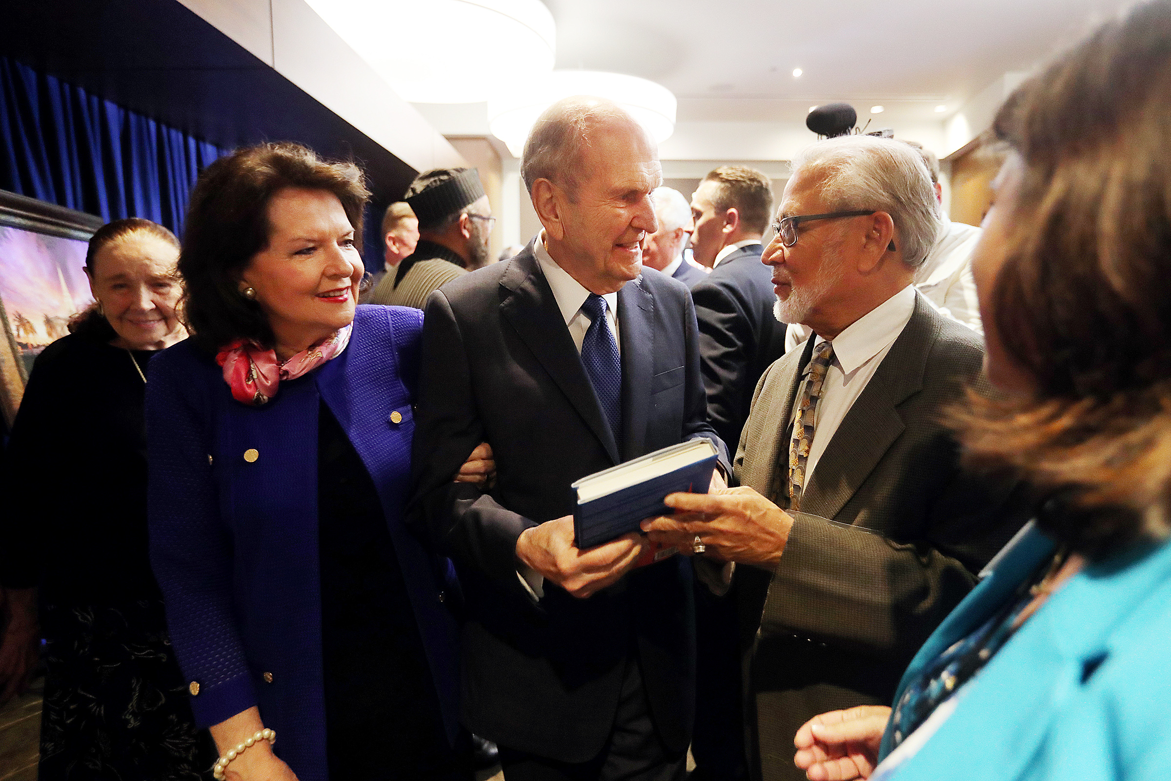 President Russell M. Nelson, is handed a book from Victor Begg as he and his wife, Sister Wendy Nelson, meet VIPs prior to a devotional at the Amway Center in Orlando, Florida, on Sunday, June 9, 2019.