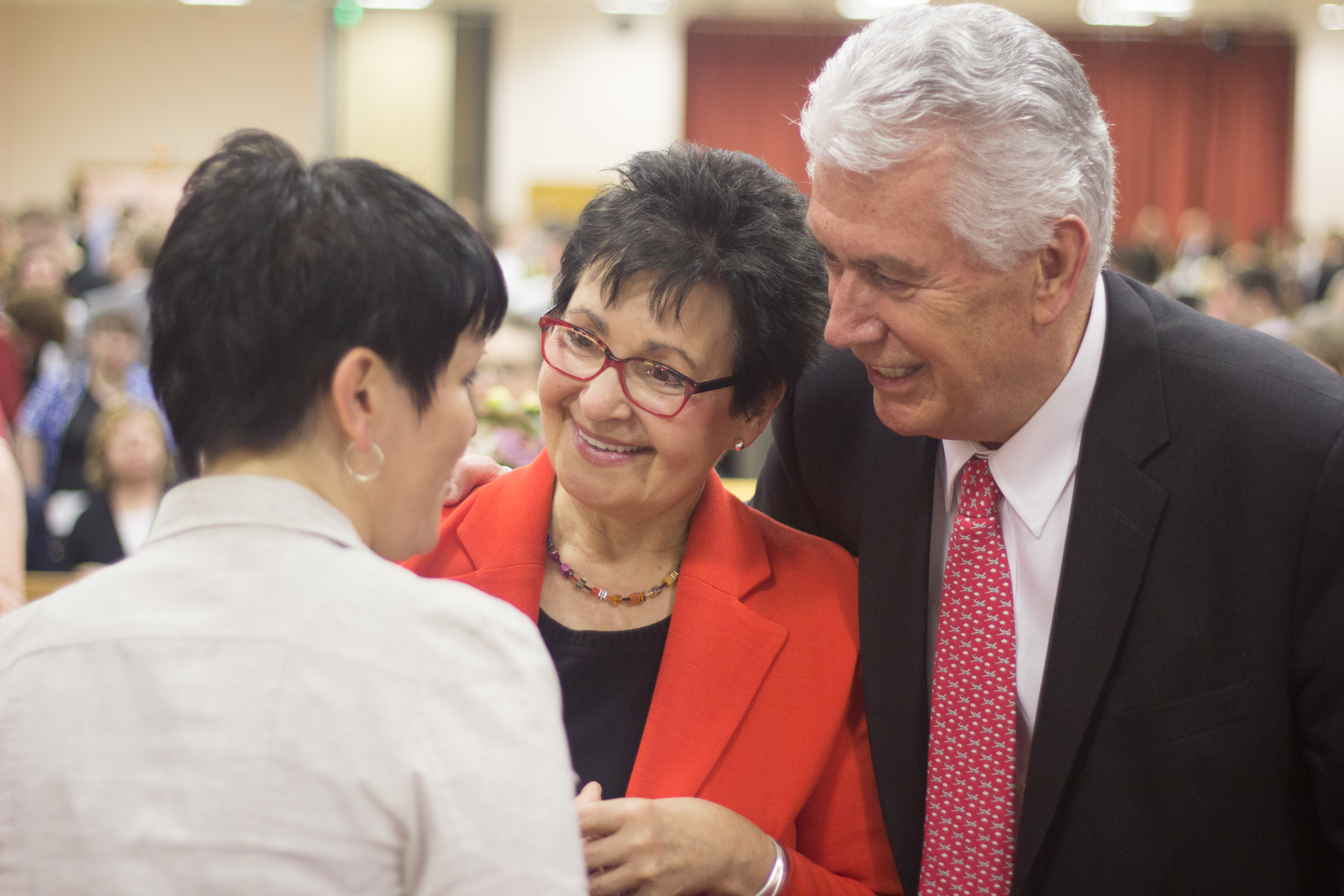 Elder Dieter F. Uchtdorf of the Quorum of the Twelve Apostles and his wife, Sister Harriet Uchtdorf, visit with a woman following the April 26, 2018, devotional with members in St. Petersburg, Russia.