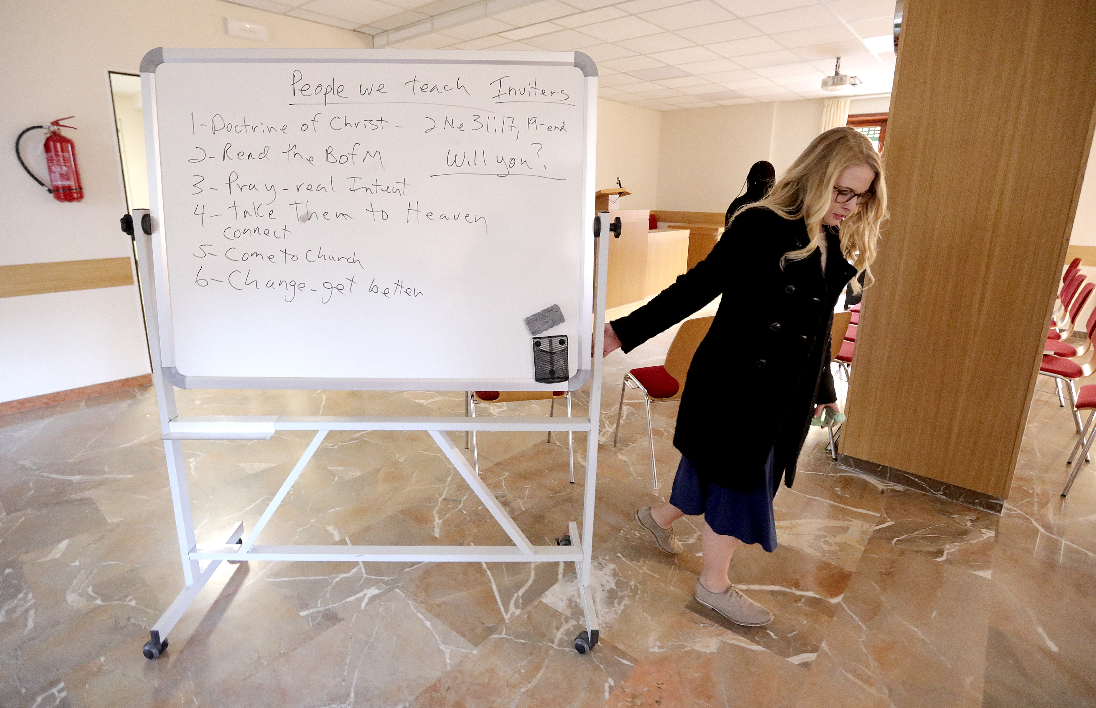 Sister Sadie Decker moves a whiteboard to assist in teaching a lesson to a recent convert at the Rome 2nd/5th wards meetinghouse in Rome, Italy, on Saturday, Nov. 17, 2018.