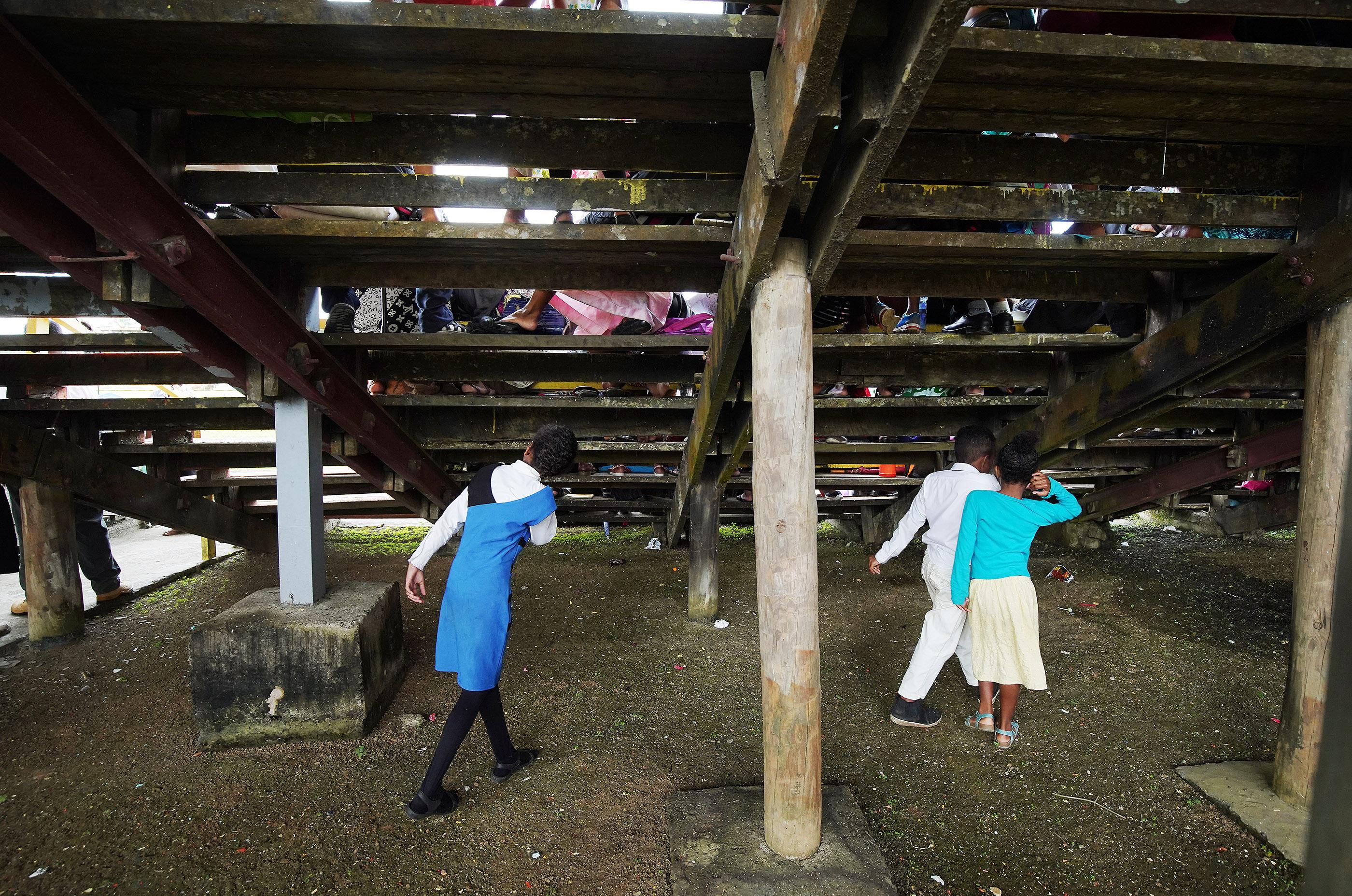 Children play under the bleachers during a devotional at Ratu Cakobau stadium in Nausori, Fiji on May 22, 2019.