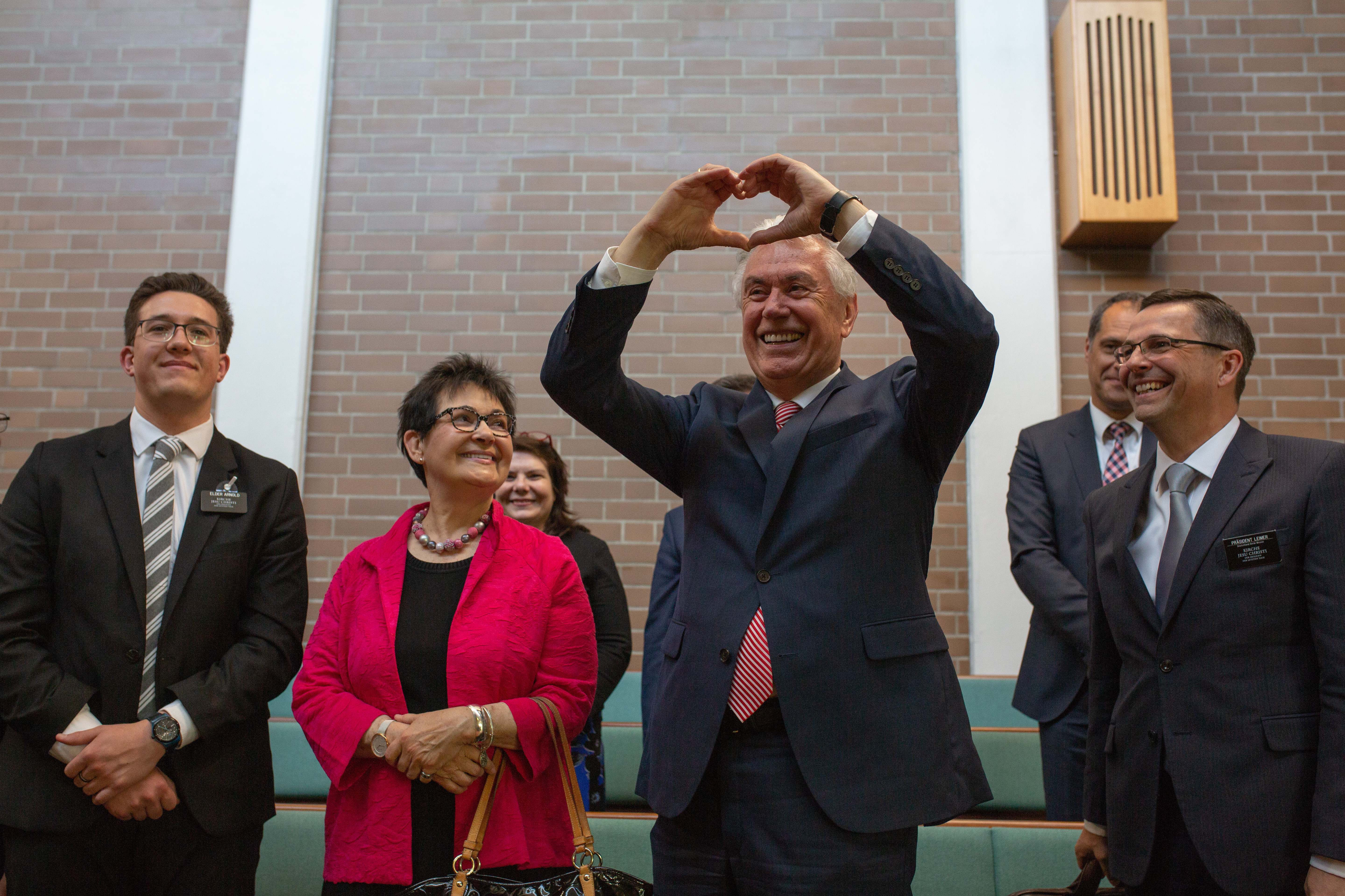 Elder Dieter F. Uchtdorf clasps his hands together to form a heart after speaking to missionaries of the Germany Berlin Mission during a mission conference in Berlin on April 26, 2019.
