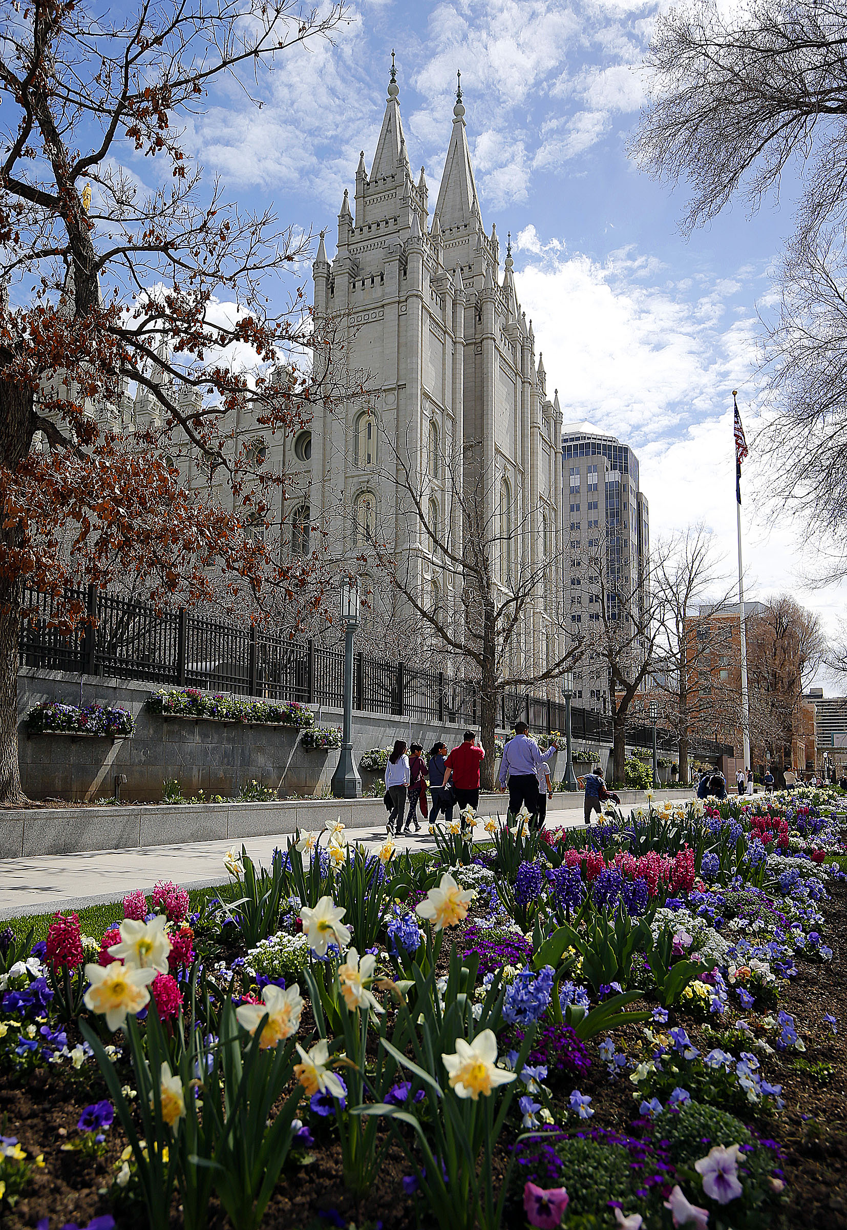 Visitors to Temple Square walk by flowers near the Salt Lake Temple of The Church of Jesus Christ of Latter-day Saints in Salt Lake City on Friday, April 5, 2019.