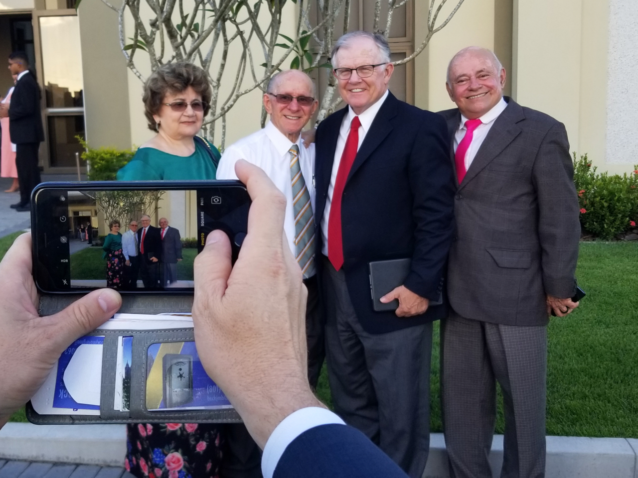 Pausing for a photo by a family member are, from left, Maria Cintra, Lino Cintra, John M. Beck, and Antonio Ferreira on June 1, 2019, outside the stake center on the grounds of the Fortaleza Brazil Temple. The Cintras and Ferreiras were among the first converts baptized in Fortaleza, in 1966, with Beck among the four missionaries who taught them.