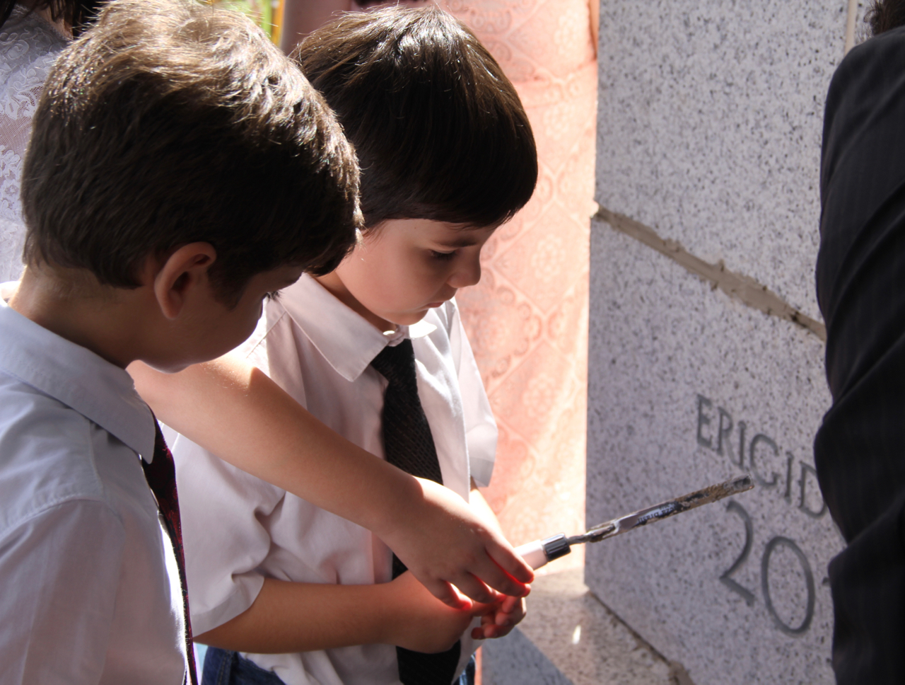 Children take turns applying mortar to the cornerstone of the Fortaleza Brazil Temple after the cornerstone ceremony had concluded Sunday, June 2, 2019.