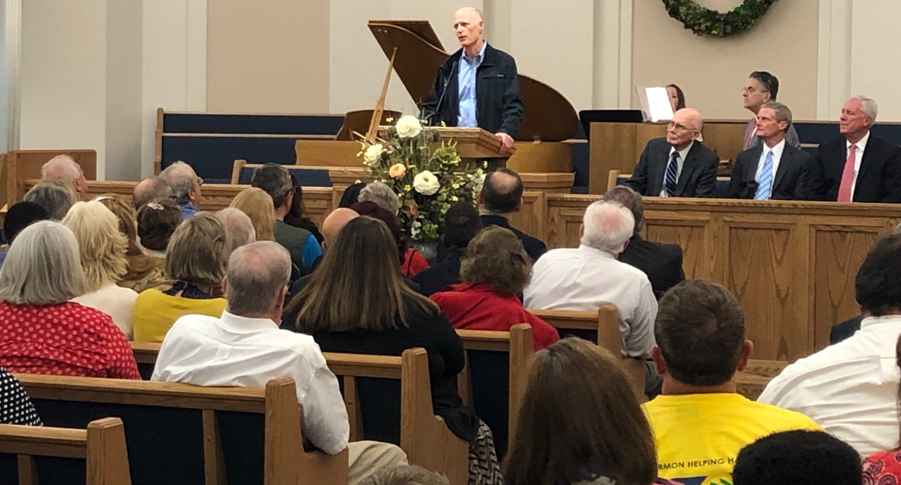 Florida Gov. Rick Scott thanks Latter-day Saints for their ongoing efforts to provide relief to those impacted by Hurricane Michael a few minutes prior to a member devotional at the Florida Tallahassee Stake Center. President Dallin H. Oaks and Elder David Bednar, seated on the podium, participated in the devotional, along with several other leaders of The Church of Jesus Christ of Latter-day Saints in the Oct. 20, 2018, event.