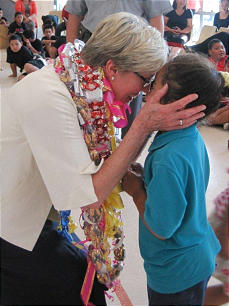 Sister Rosemary Wixom greets a child by observing local tradition and rubbing her nose against his.