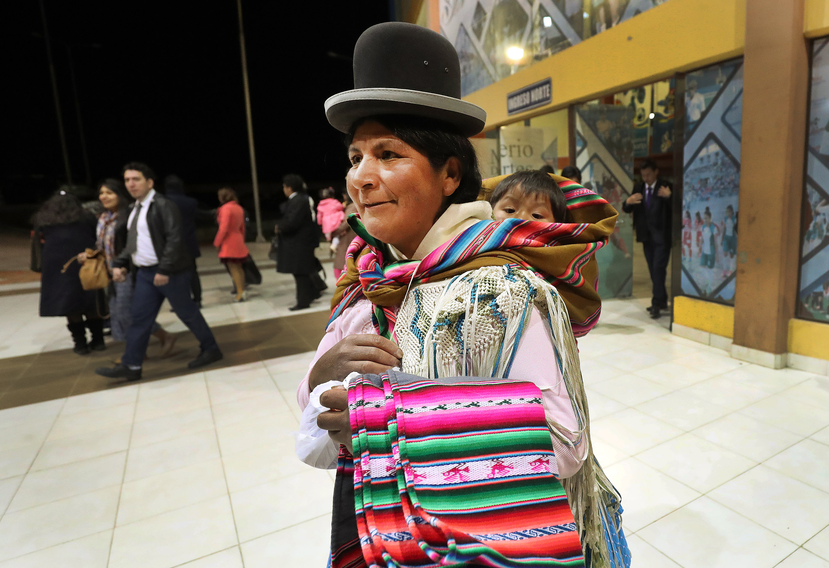 A woman wearing traditional clothing carries her child after hearing President Russell M. Nelson of The Church of Jesus Christ of Latter-day Saints speak in La Paz, Bolivia on Oct. 21, 2018.