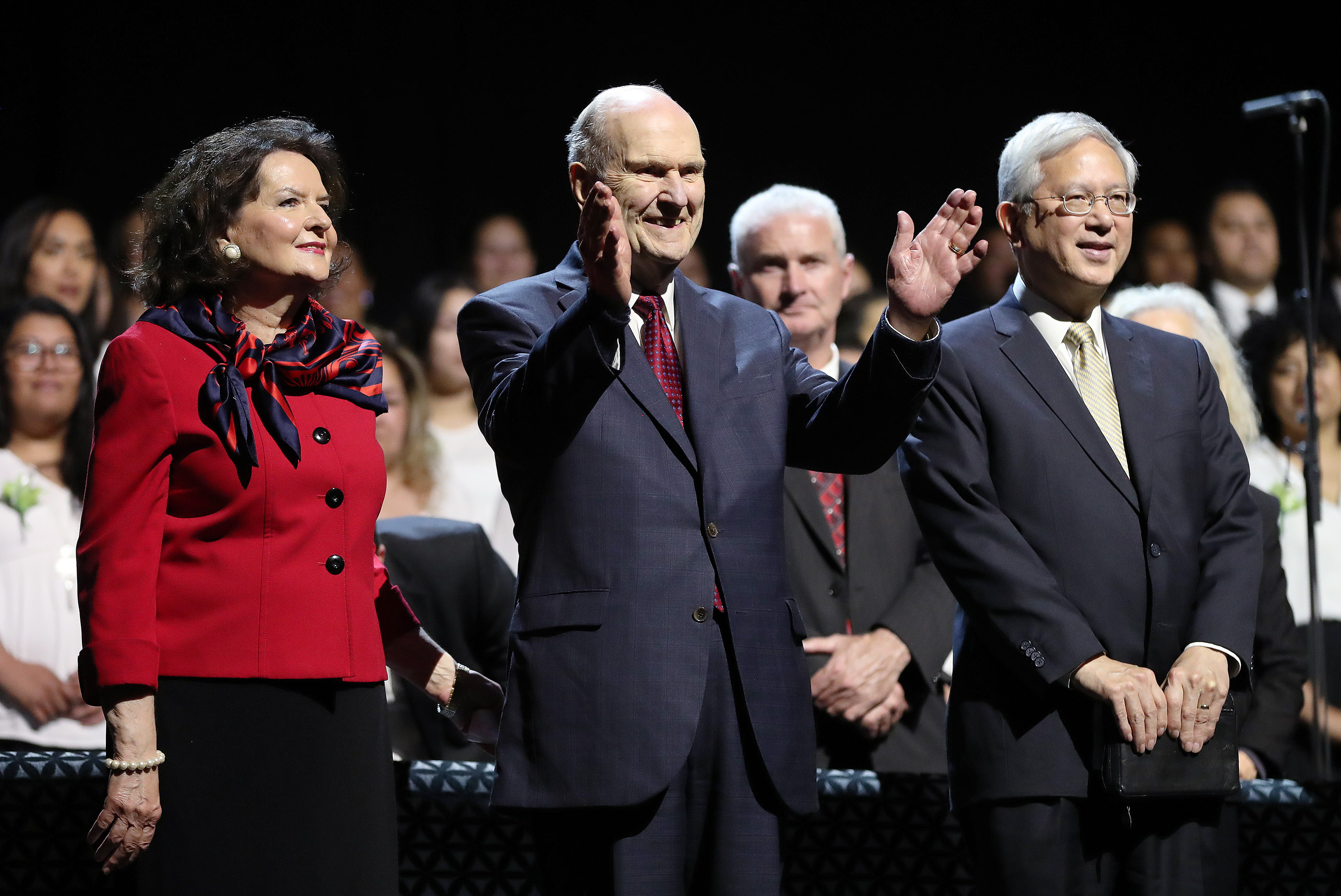 President Russell M. Nelson of The Church of Jesus Christ of Latter-day Saints and his wife, Sister Wendy Nelson, and Elder Gerrit W. Gong of The Church of Jesus Christ of Latter-day Saints' Quorum of the Twelve Apostles acknowledge attendees prior to a devotional in Spark Arena in Auckland, New Zealand, on May 21, 2019.