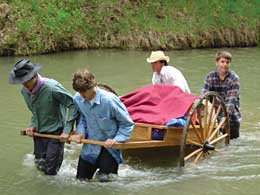 In one of the more popular activities during the Carrollton Texas Stake trek, young men push and pull a handcart in a river in a state park near Dallas.
