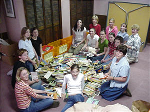 Young women help Jessica Greene gather books for her former students in China.