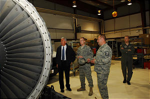 President Dieter F. Uchtdorf with Staff Sgt. Luke Hurst and Master Sgt. Daryl Chadwick examine an aircraft engine in a maintenance shop for repairs.