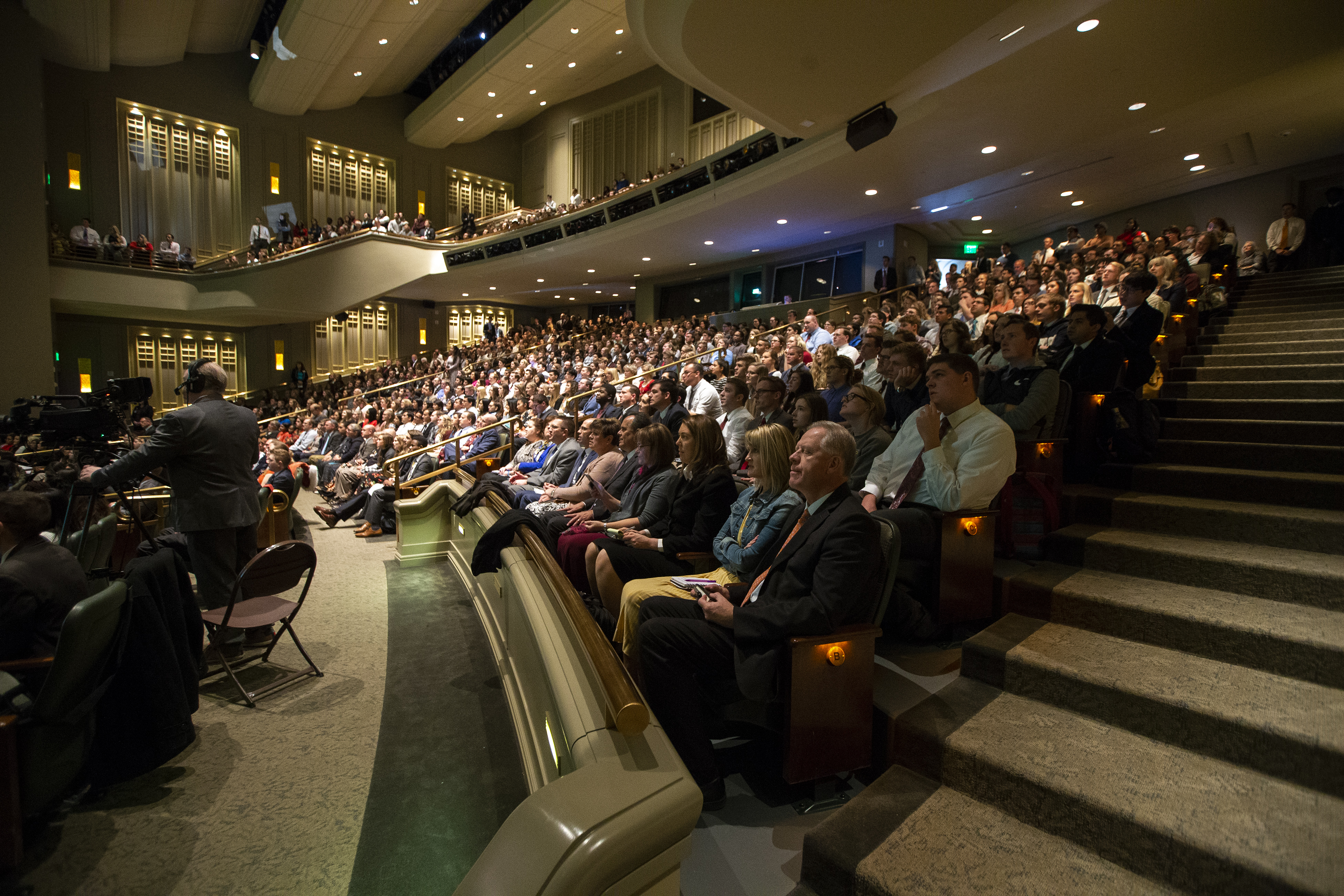 Audience members sing the opening hymn prior to President Henry B. Eyring speaking to LDS Business College students during a devotional in the Conference Center Theater in Salt Lake City on Tuesday, Nov. 6, 2018.