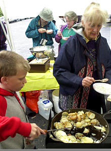 Meriam Kienke and her 11-year-old grandson, Russell Sheehy, cook potatoes on an outdoor gas unit to demonstrate alternative cooking methods in case of an emergency, Saturday, May 11, 2002. Clark and Gayle Gable, Salt Lake, try a sample. (Submission date: 05/11/2002)