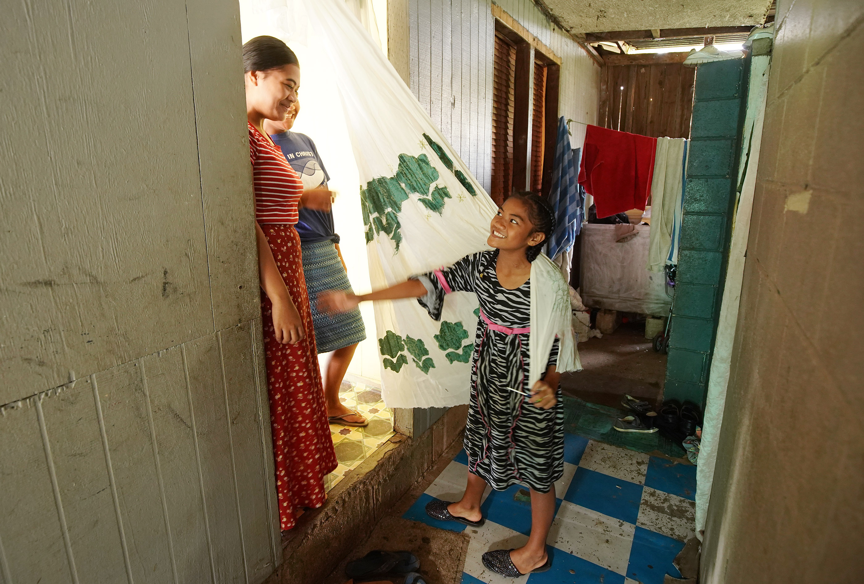 Falakika talks with her sisters Telesia and Uinise at their his home in Tonga on May 23, 2019. Their father is bishop of his ward and has 10 children and one grandchild.