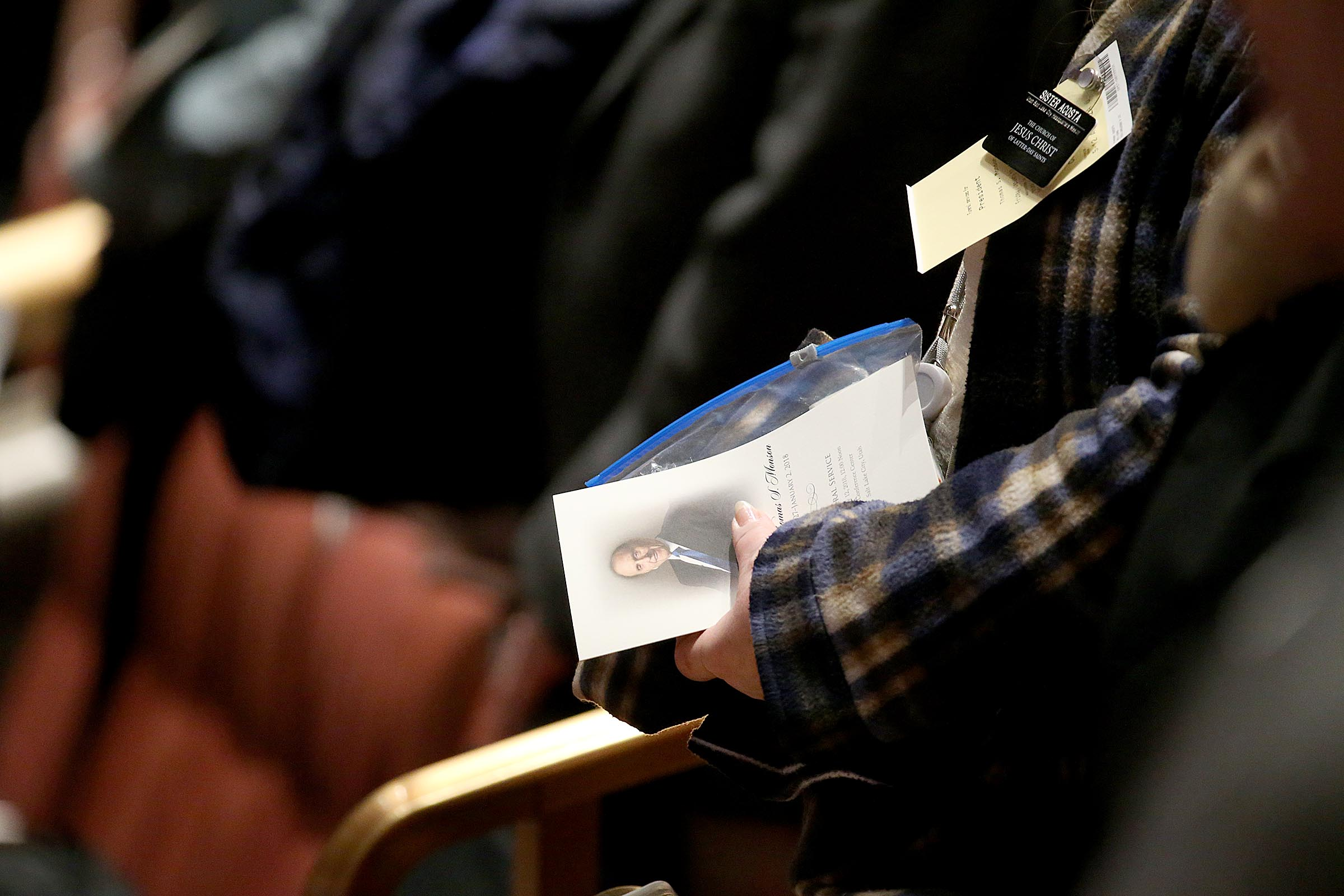 A mourner holds a program while waiting for Church President Thomas S. Monson's funeral to begin at the Conference Center in Salt Lake City on Friday, Jan. 12, 2018.