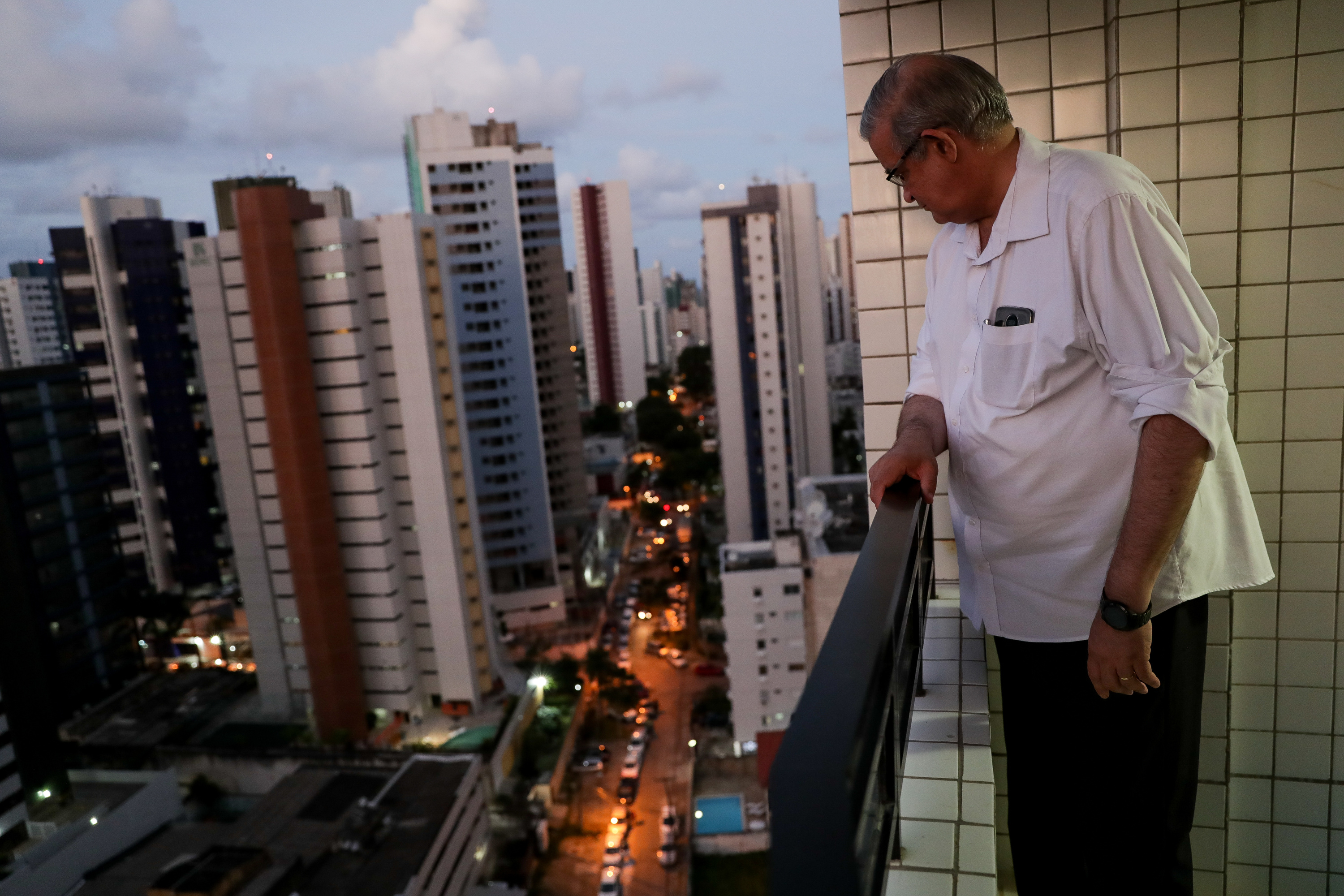 Paulo Almeida Saihg looks down at the street from his high-rise apartment in Recife, Brazil, on Saturday, May 26, 2018.