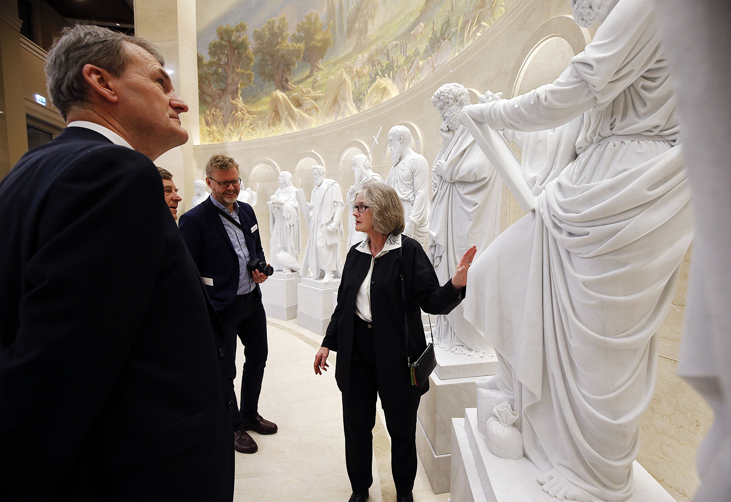 Vicar priest Steffen Ringgaard Andresen, architect Niels Valentiner and Jonas Bencard listen as Susanne Torgard, curator at the Church of Our Lady in Copenhagen, Denmark, talks about the digital, 3-D marble replicas of the ancient apostles at the Rome Temple Visitors' Center in Rome, Italy, on Wednesday, Jan. 16, 2019. The Church of Our Lady home to the original statues.