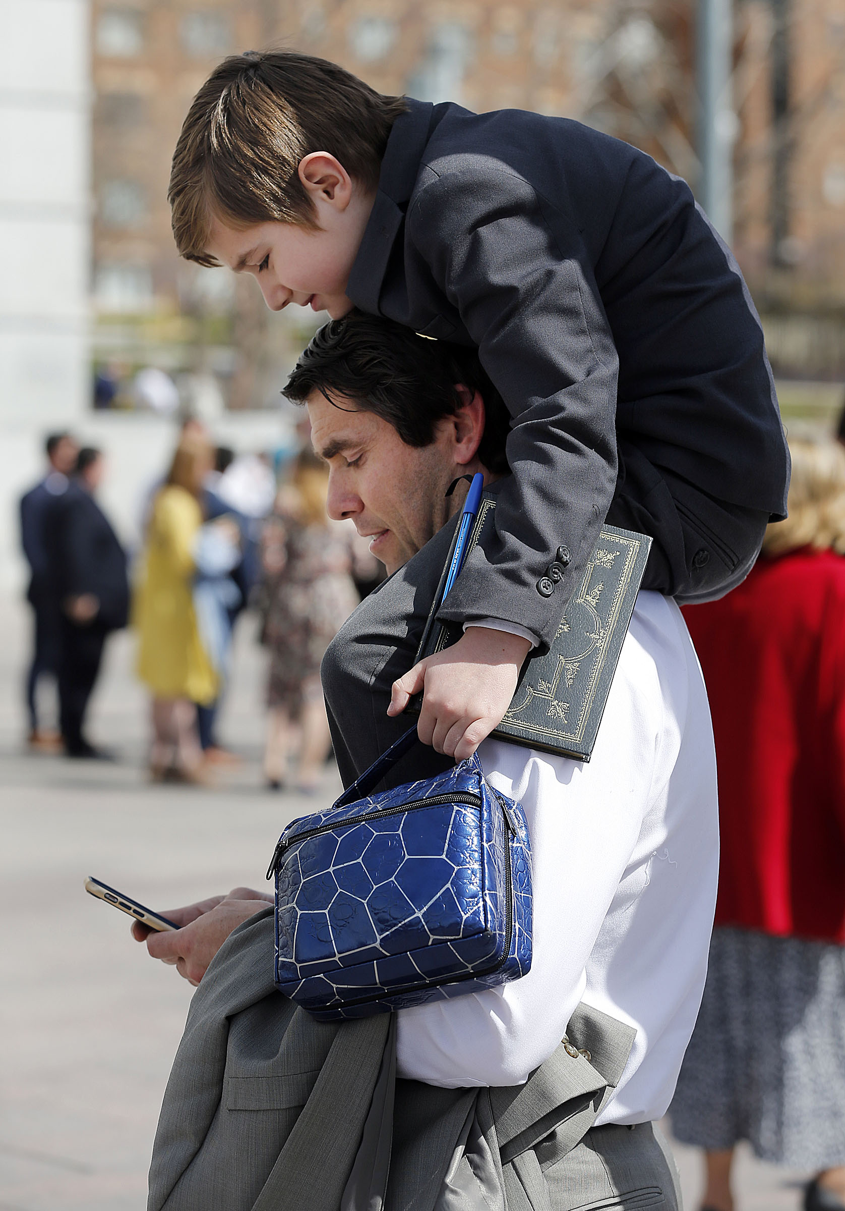 Joey O'Loughlin and his son Joseph Michael O'Loughlin wait outside the Conference Center following the Saturday morning session of the LDS Church's 188th Annual General Conference in Salt Lake City on Saturday, March 31, 2018.