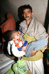 Pakistani earthquake victim, with sack of Church aid, holds his injured child in Hilcot Mansehra village. The child's mother died during the disaster. The Church distributed tents, blankets and food in the village.