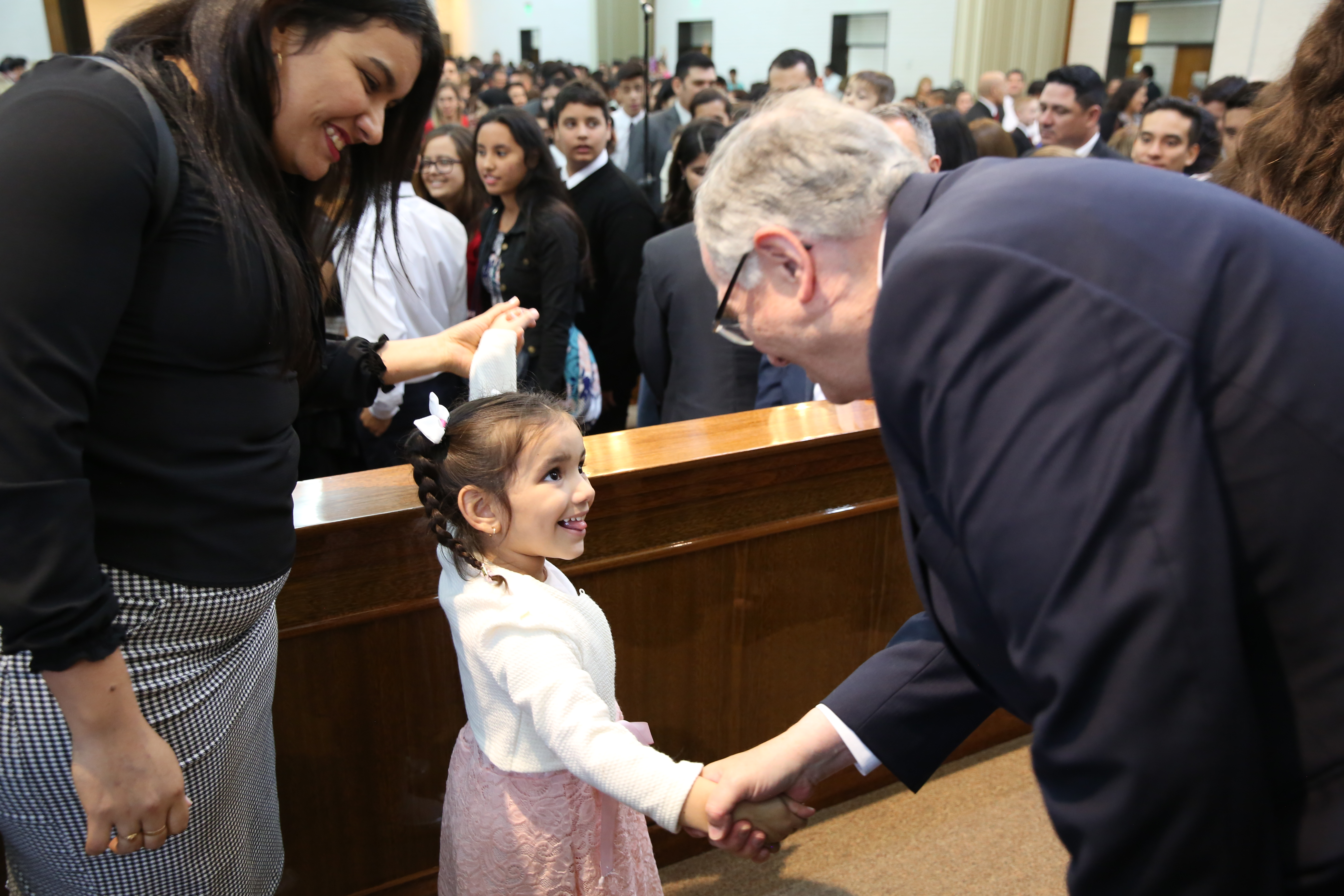 Elder Neil L. Andersen shakes hands with a young girl following a stake meeting in Resistencia, Argentina, in April 2019.