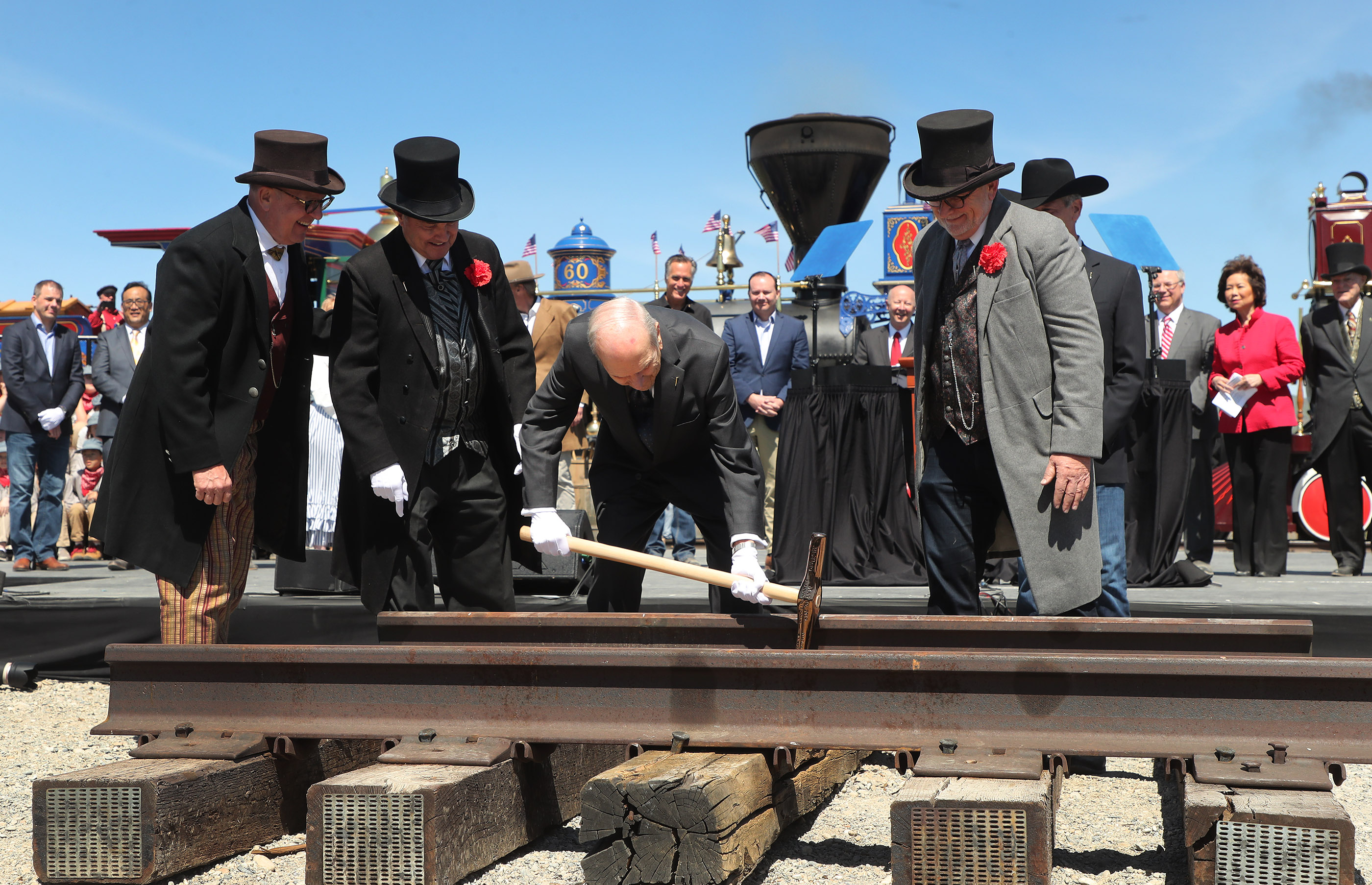 President Russell M. Nelson of The Church of Jesus Christ of Latter-day Saints, center, drives a golden spike during the 150th anniversary celebration of the transcontinental railraod at the Golden Spike National Historical Park at Promontory Summit on Friday, May 10, 2019.