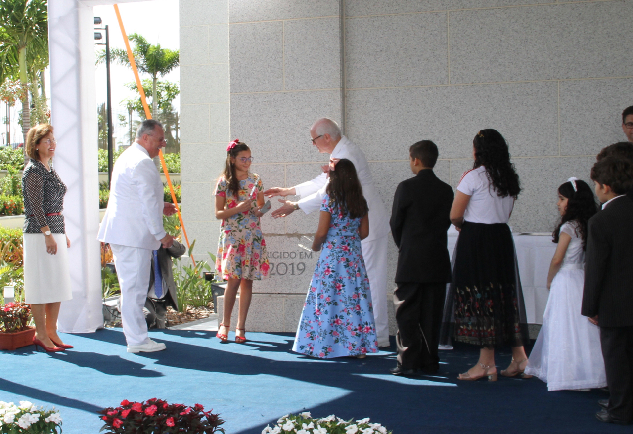 Elder Ulisses Soares of the Quorum of the Twelve Apostles and his wife, Sister Rosana Soares, left, join with Elder Larry Y. Wilson, a General Authority Seventy and executive director of the Temple Department, in assisting a handful of youth apply mortar to the cornerstone of the Fortaleza Brazil Temple on Sunday, June 2, 2019.
