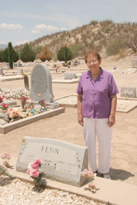 Louise Fenn Larson stands in Pomerene Cemetery near headstone marking her parents' graves. They came to Pomerene in 1912.