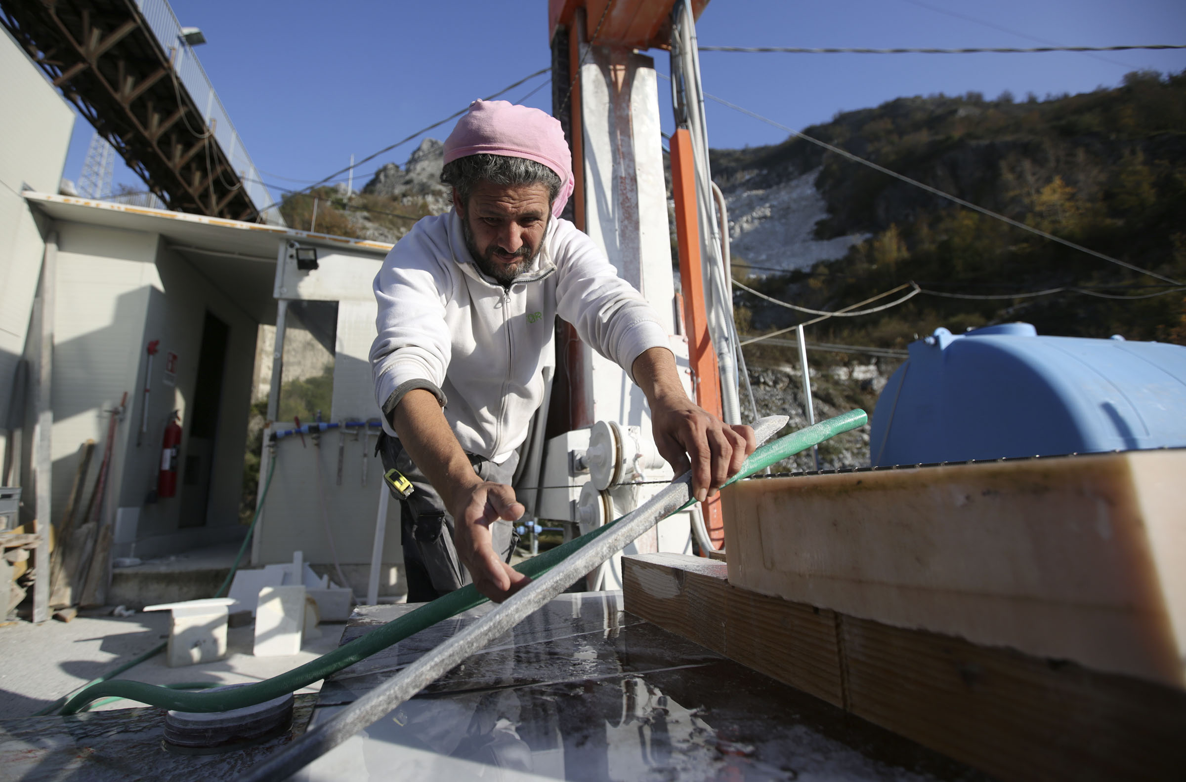 Simone Zanaglia measures where to cut Portuguese pink marble at TORART in Carrara, Italy, on Thursday, Nov. 15, 2018.