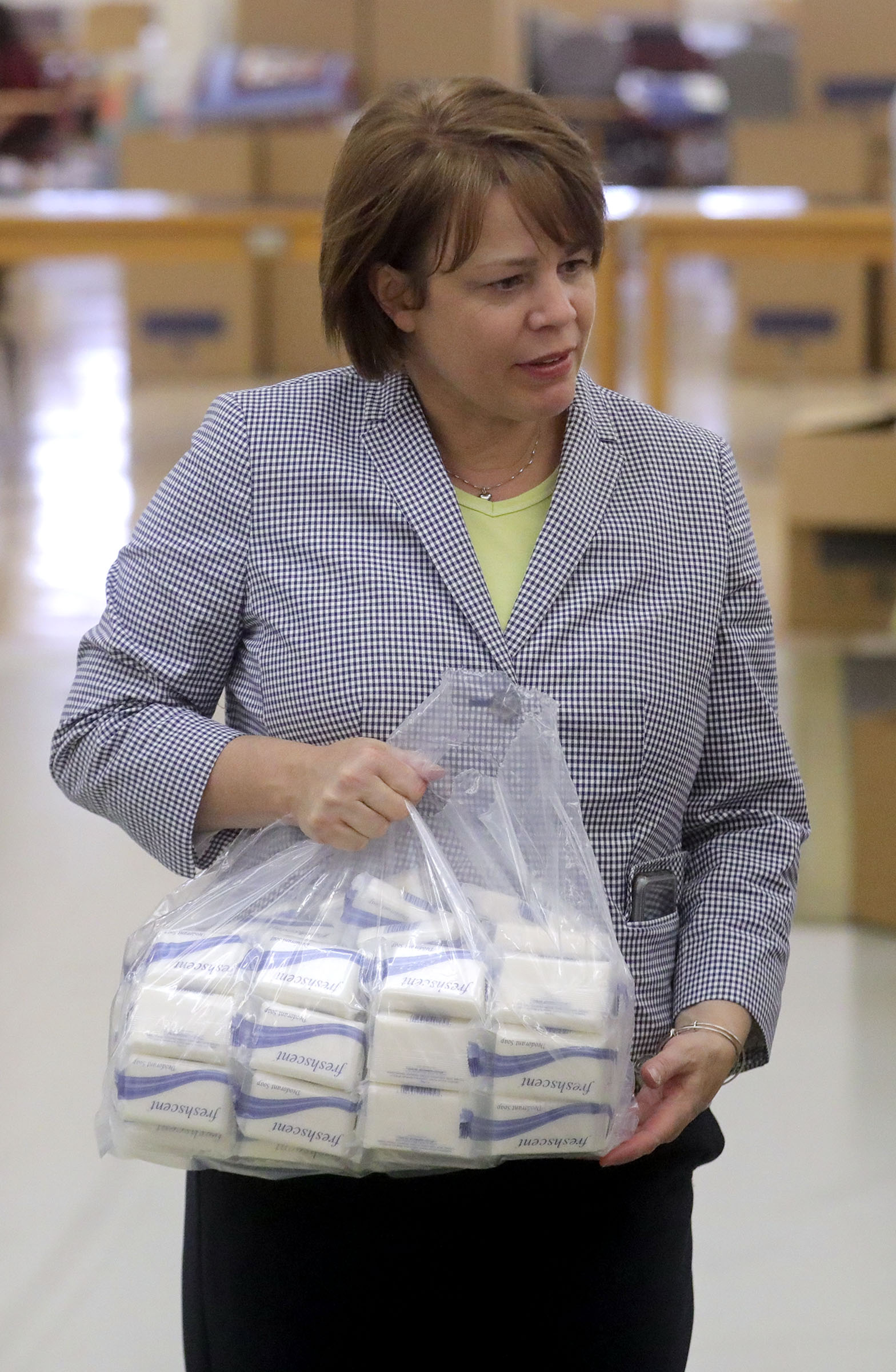 Sister Sharon Eubank, first counselor in the Relief Society general presidency, carries a bag of soap as spouses of U.S. governors take part in a service project at the Latter-day Saint Humanitarian Center in Salt Lake City on Thursday, July 25, 2019.