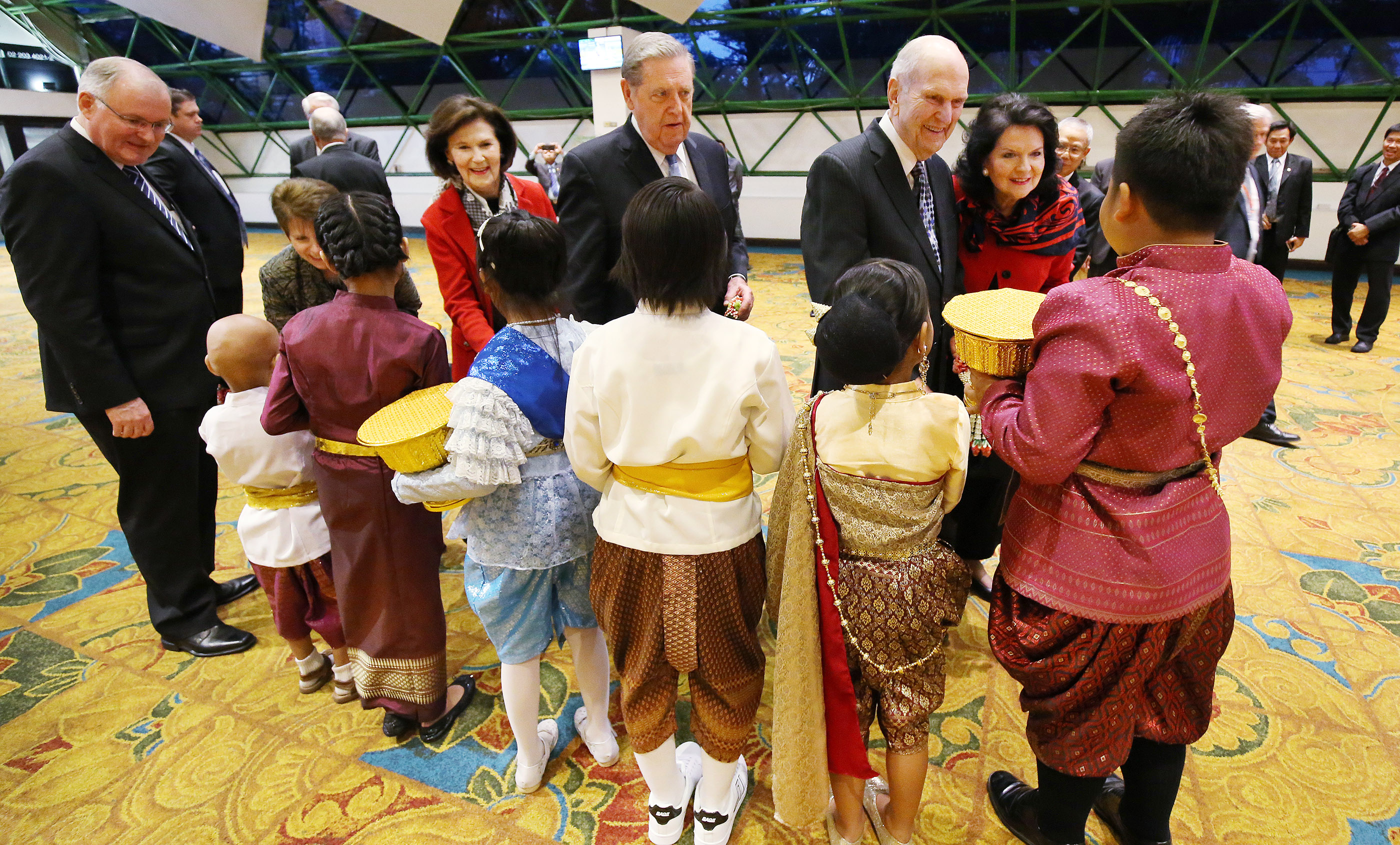 Russell M. Nelson and his wife, Sister Wendy Nelson, and Elder Jeffrey R. Holland, Quorum of the Twelve Apostles, and his wife, Sister Patricia Holland, are greeted and given flowers by Primary children in Bangkok, Thailand, on Friday, April 20, 2018.