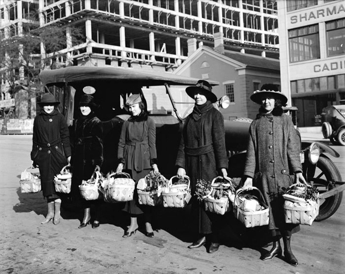 Women hold eight baskets of food on a Salt Lake City street in 1918.