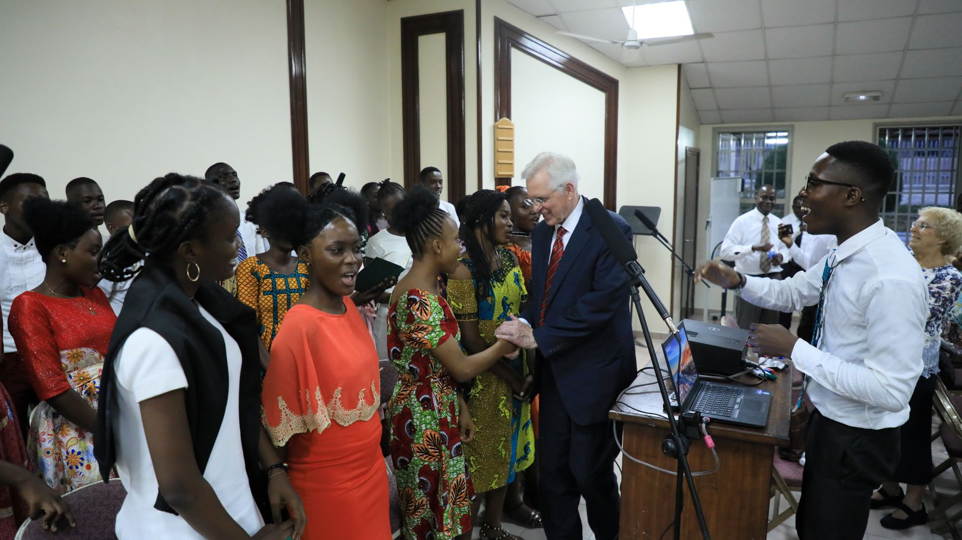 Elder D. Todd Christofferson shakes the hands of Latter-day Saints gathered for a member devotional in Cote d'Ivoire.