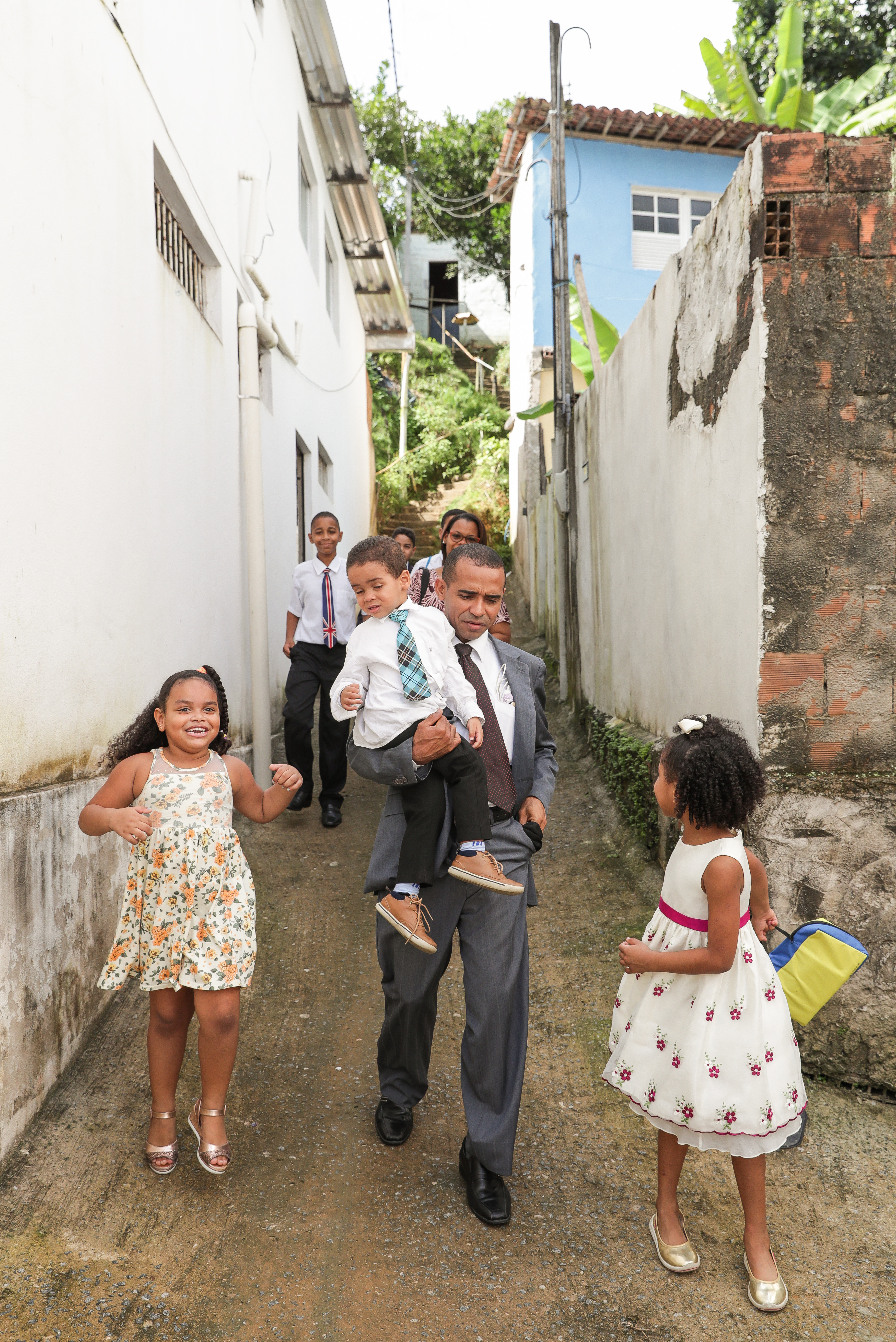 Edivaldo Brito carries his son, Helã, 3, while leaving for church with family members, including his niece, Lais Brito, 4, left, and daughter, Rebeca Brito, 6, in Cabo de Santo Agostinho, Pernambuco, Brazil on Sunday, May 27, 2018.
