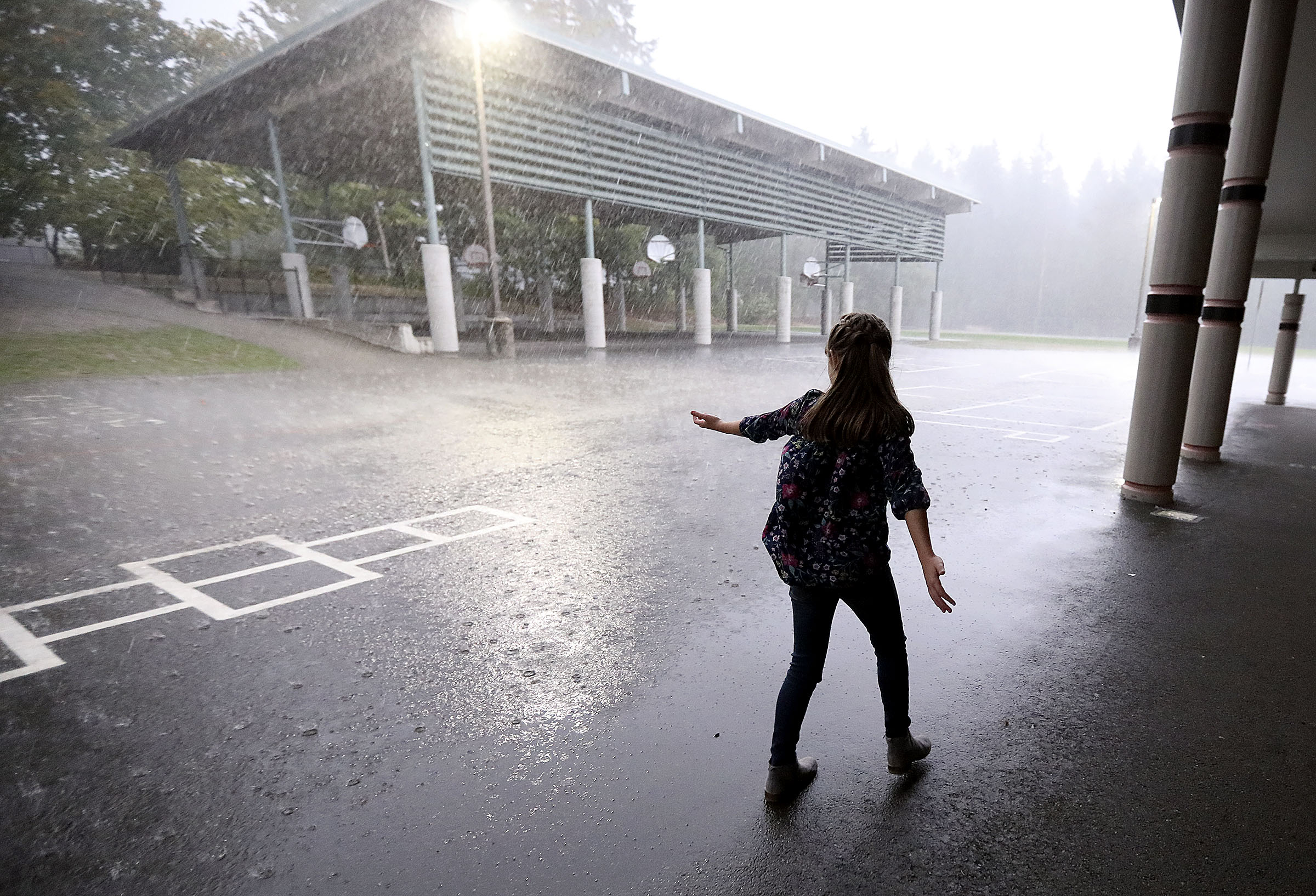 Emilia Allen watches a heavy rainfall near her home in Renton, Wash., on Friday, Sept. 14, 2018.